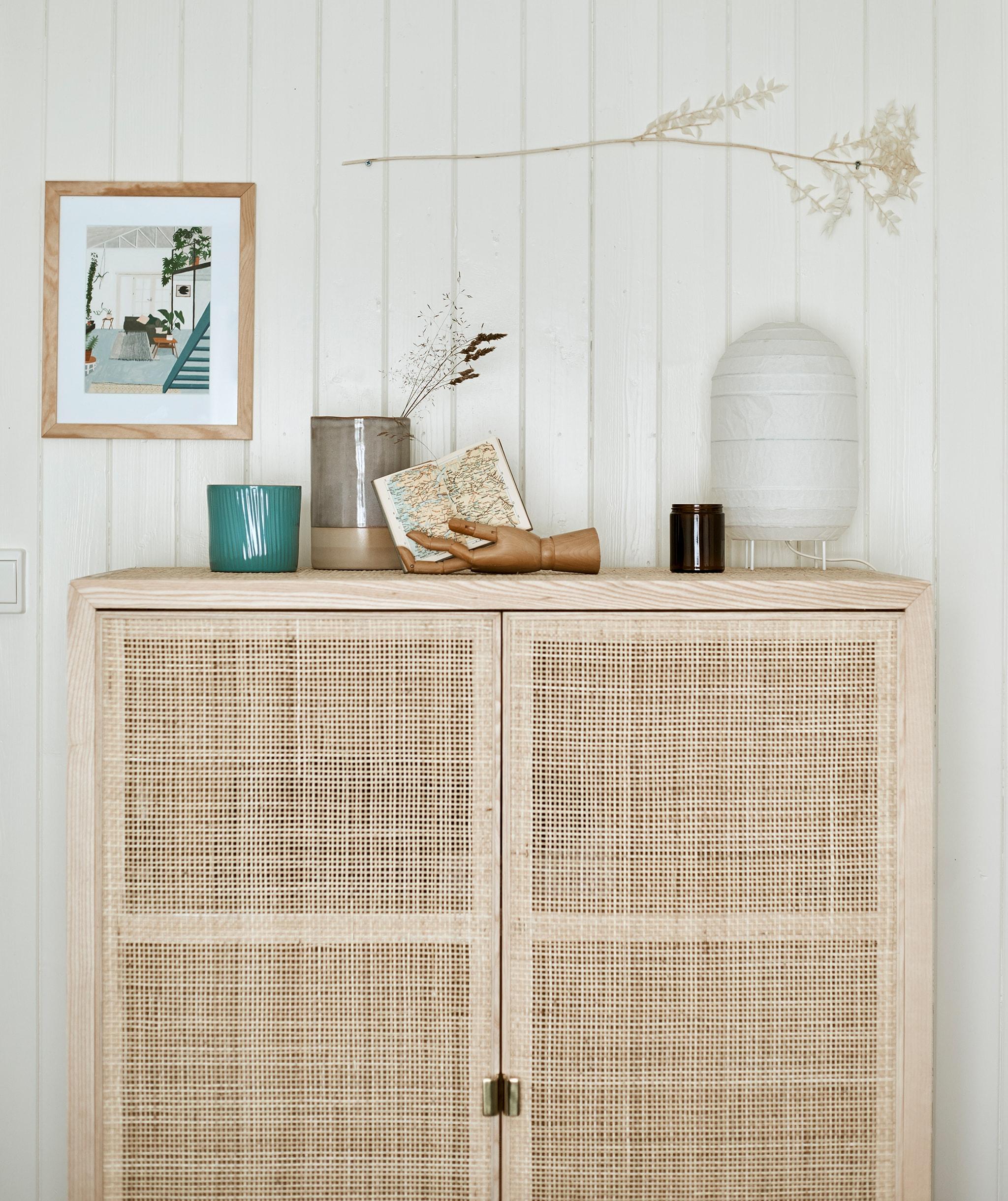 配以織藤櫃門的高身木製貯物櫃,櫃上有紙燈籠和其他擺設,背後的牆壁舖上木牆板。