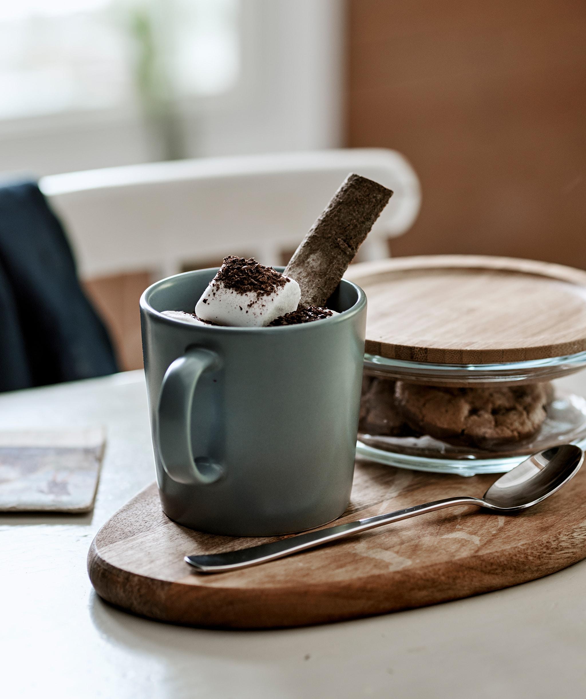 砧板上的灰藍色水杯有添加棉花糖的熱朱古力,旁邊的竹蓋玻璃瓶內有曲奇餅。