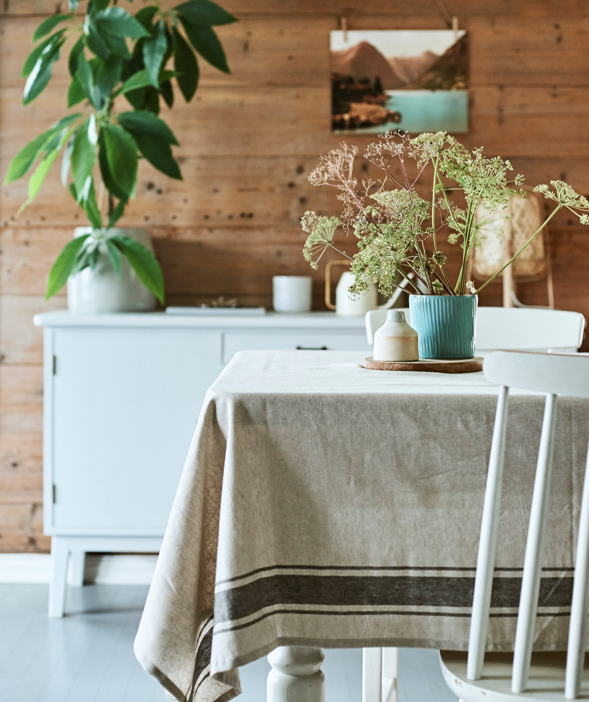 A rustic dining room with wood table covered with linen cloth and a centrepiece of wild flowers in a blue ridged plant pot.