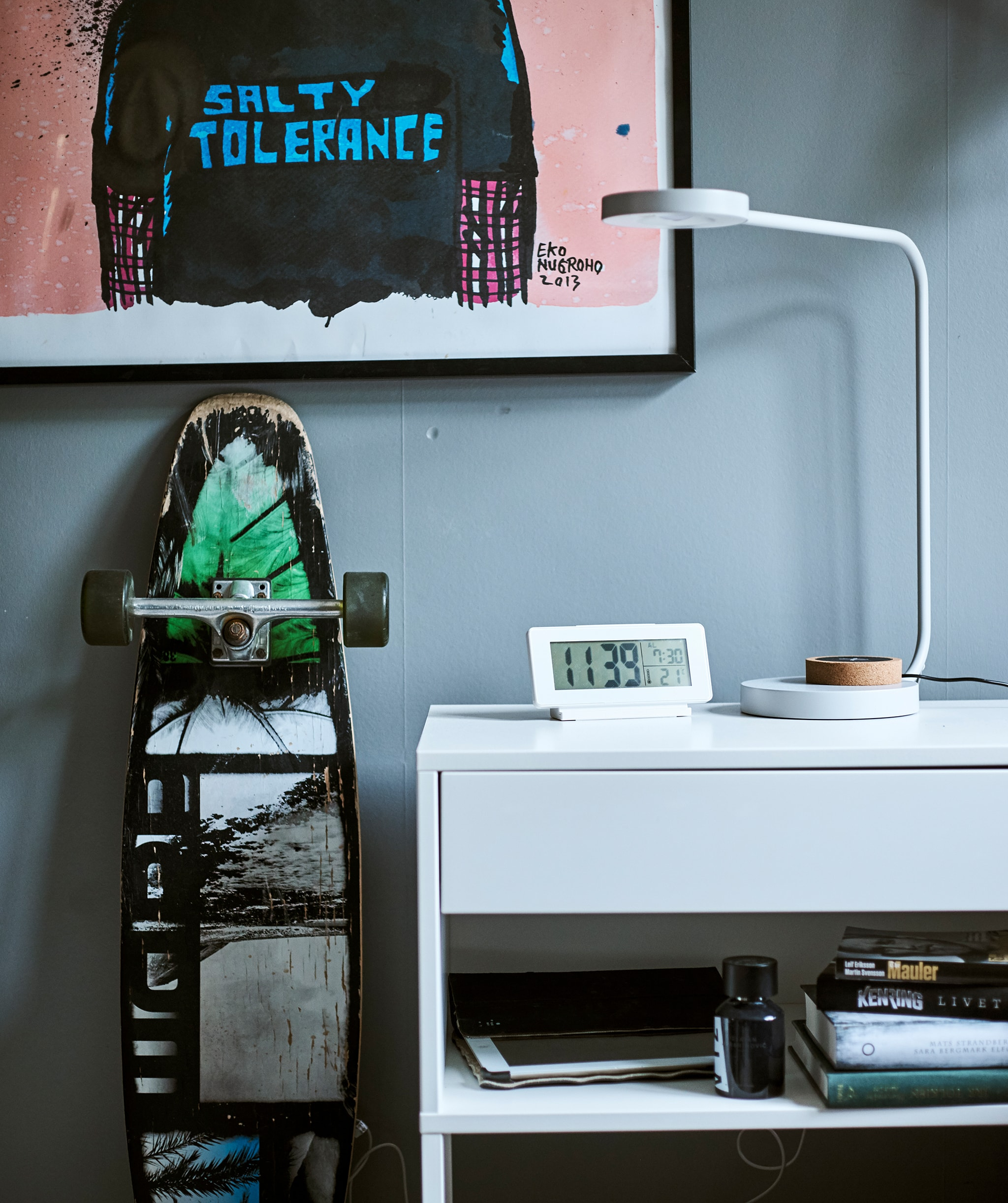 A white desk with built-in shelf, on top is a desk lamp and digital clock, graffiti art hangs on the wall above a skateboard.