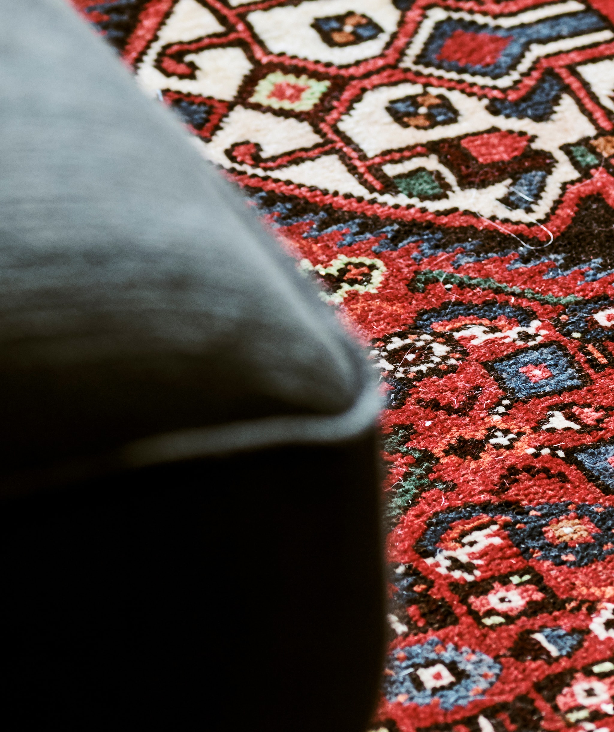 Detail of a Persian rug woven into a pattern with blue and green shapes on a red background
