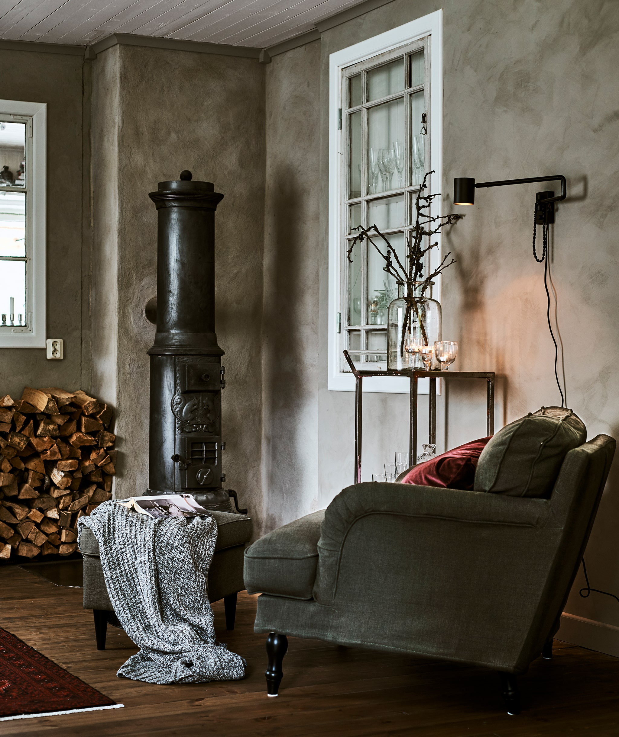 Corner of a grey-walled room with a green armchair, red cushion and footstool next to wood-burning stove and wood pile.