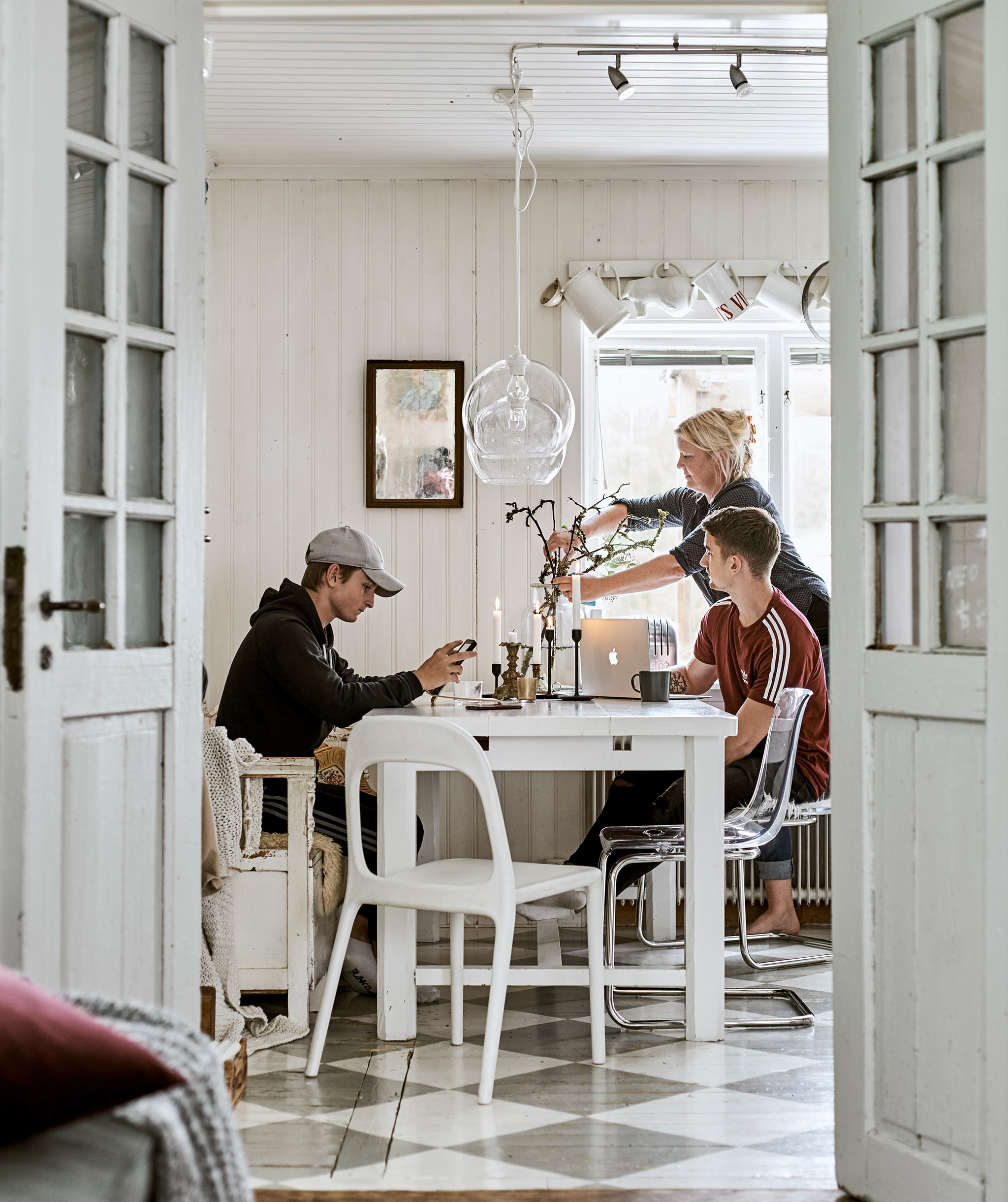 French doors open to a dining room with checked floor. A family sits at a white dining table, glass lamps hang overhead.