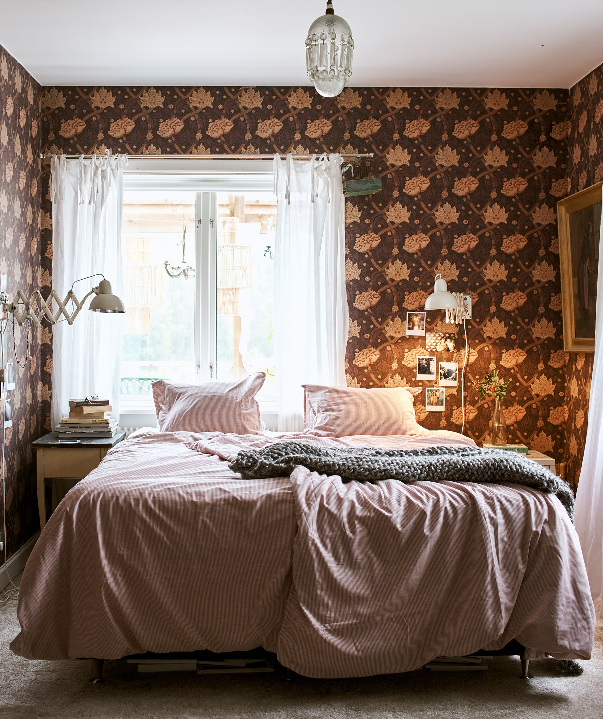 A bed made up with pink bedding and a grey throw in the centre of a room with a chandelier and floral patterned wallpaper.
