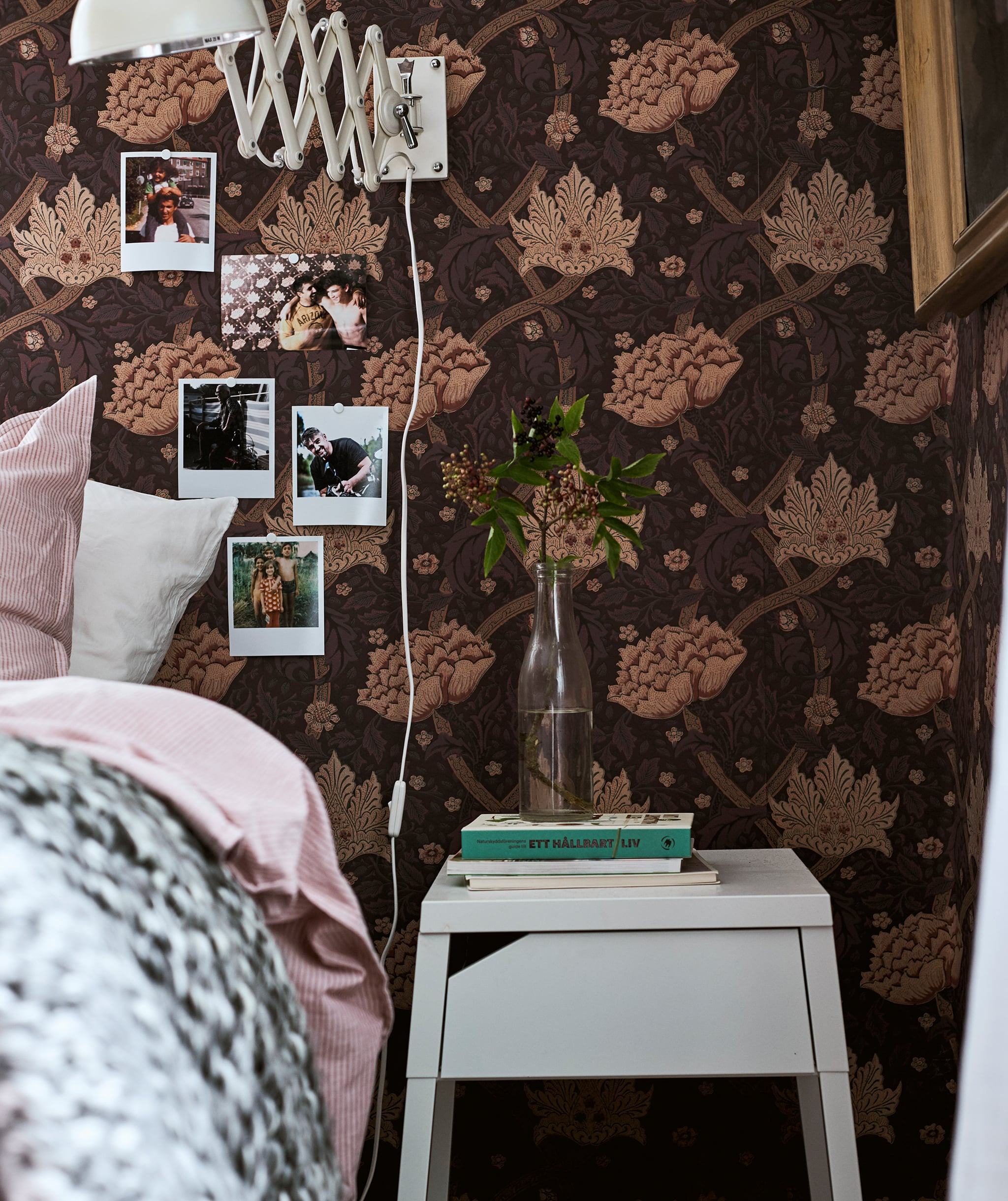 A bed with pink bedding next to a white bedside table with books and a stem in a vase, Polaroids are on the papered wall.
