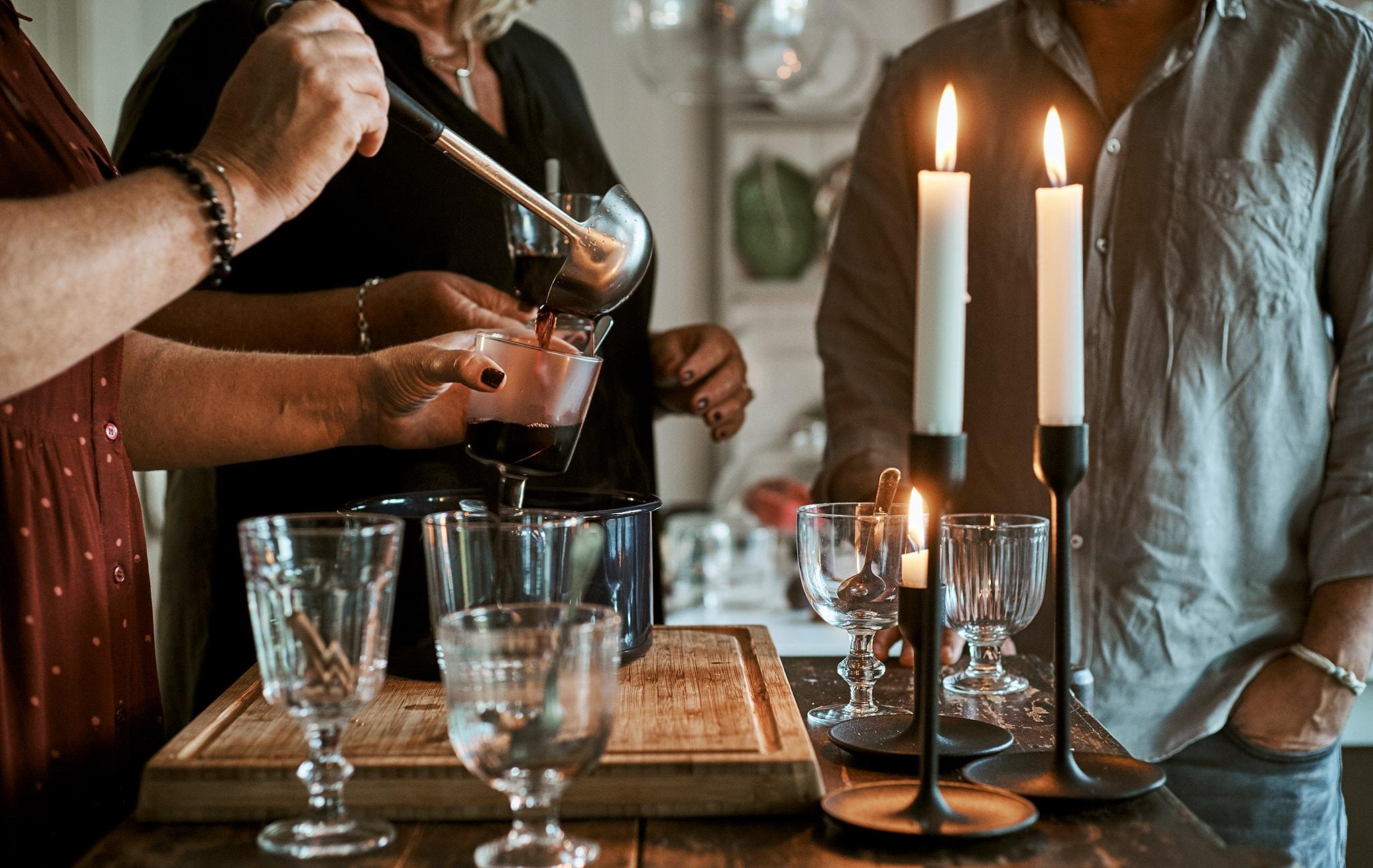 多人站在廚房島形工作檯旁邊,檯上有杯、點亮的蠟燭和一鍋熱賓治,其中一人將飲品舀進杯內。