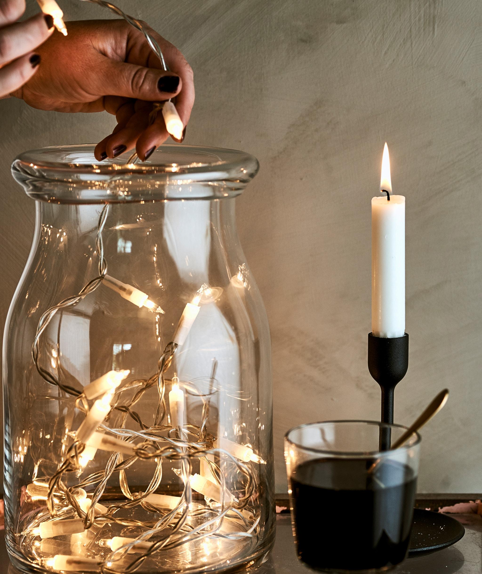 一名女子將裝飾燈串放入玻璃瓶,旁邊有一杯酒和插在黑色燭台上的蠟燭。