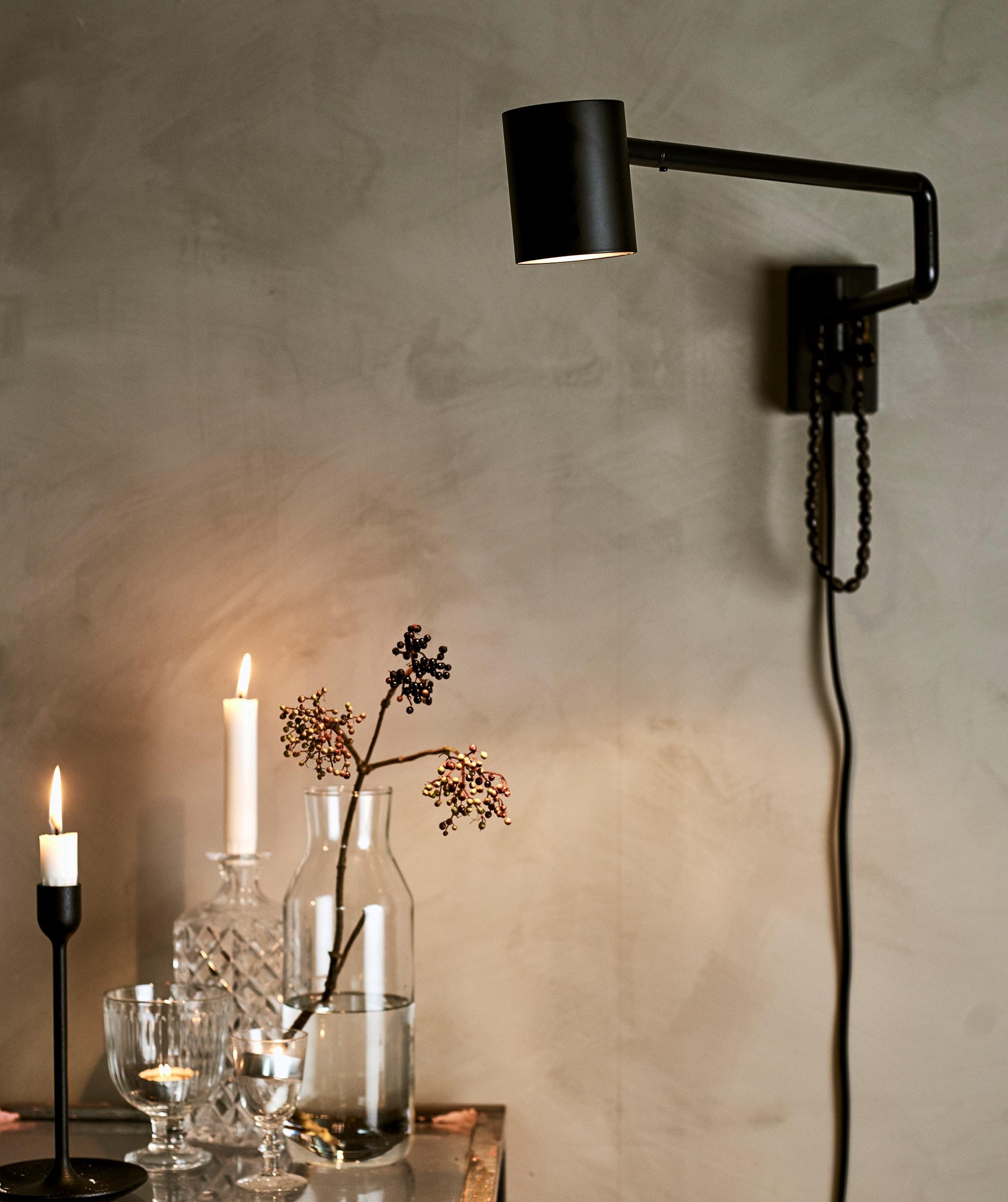 灰色牆上裝有一盞黑色壁燈,照亮玻璃檯上的各種玻璃器皿、蠟燭和茶燭。