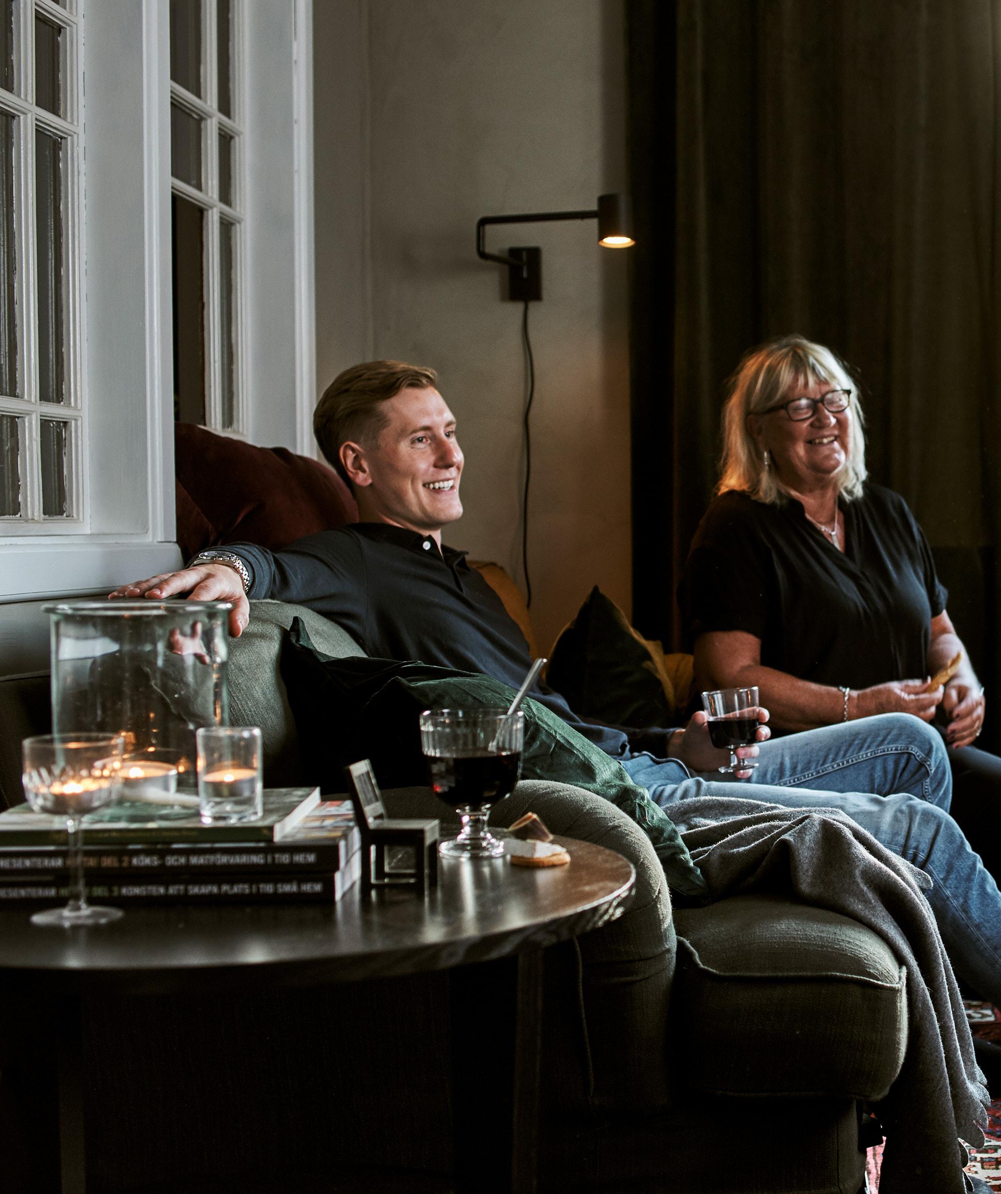 一男一女坐在綠色梳化上,梳化上有咕𠱸和暖氈,茶几上的玻璃杯內有飲品,另外還有茶燭和書。