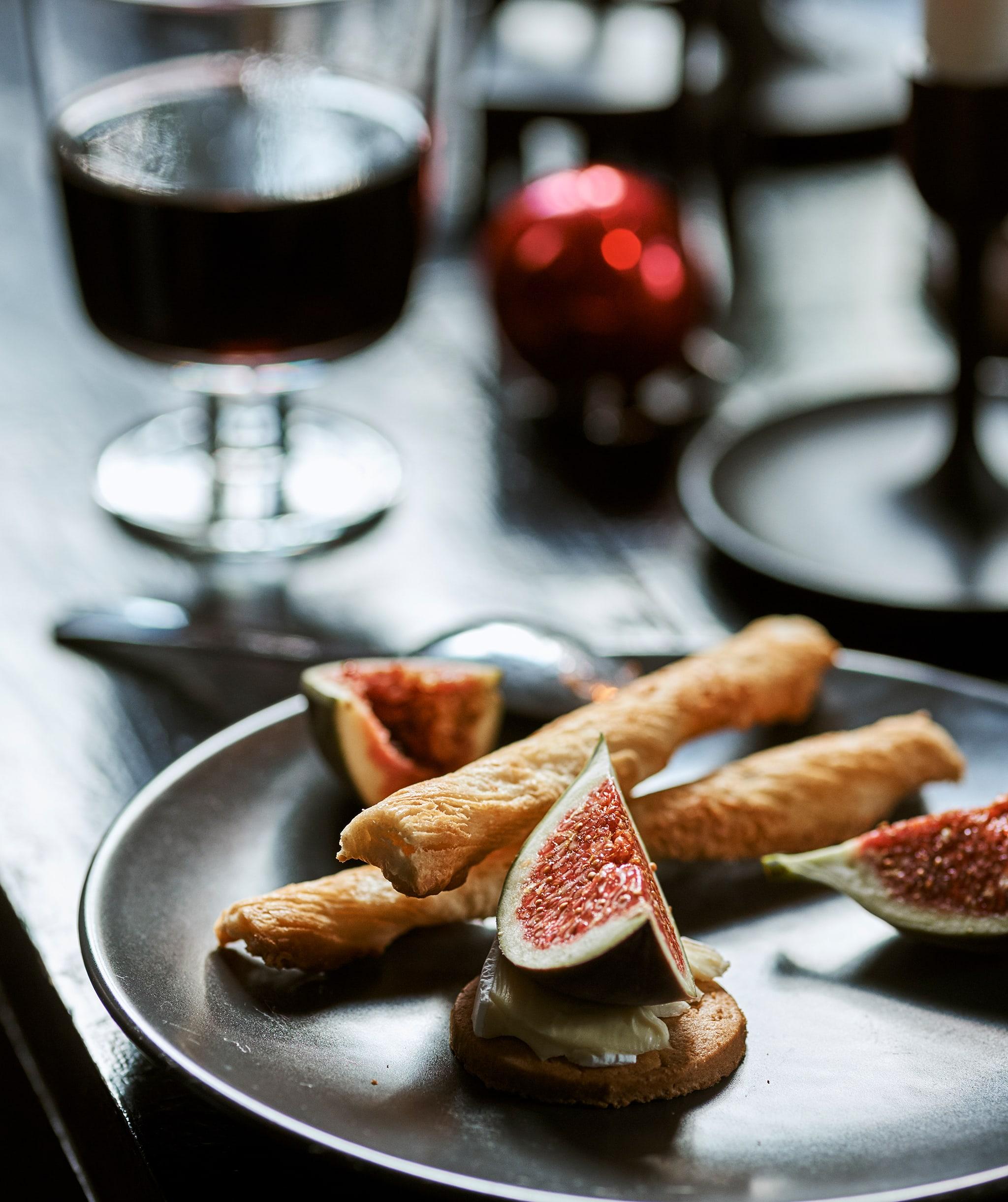 餐檯上有一碟派對食物,包括無花果、芝士、餅乾、麵包脆條,另外還有一杯酒和紅色聖誕掛飾。