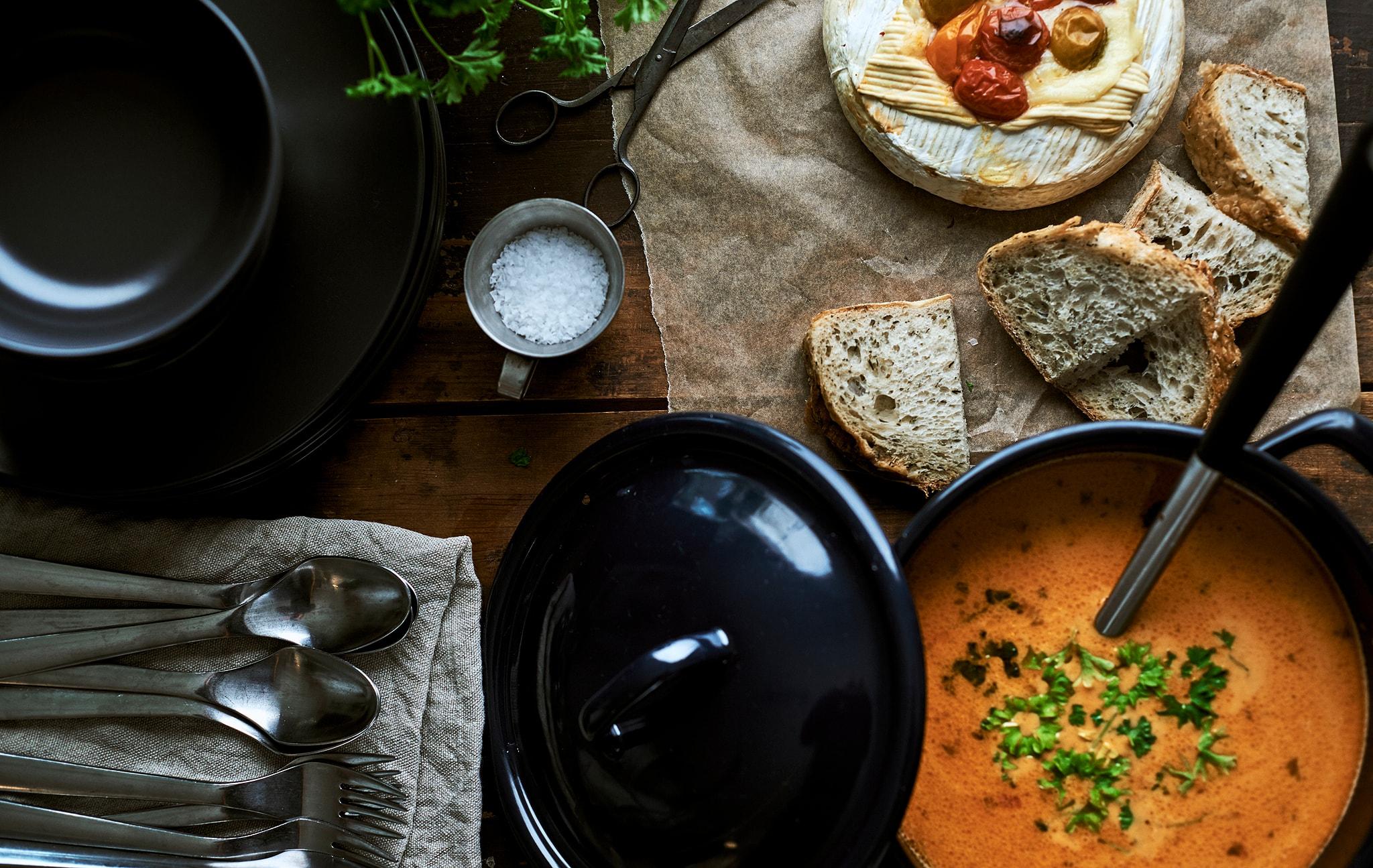 藍色搪瓷鍋內有湯和長勺,旁邊有切片的麵包、焗金文拔芝士、一疊碗碟、餐巾和餐具。