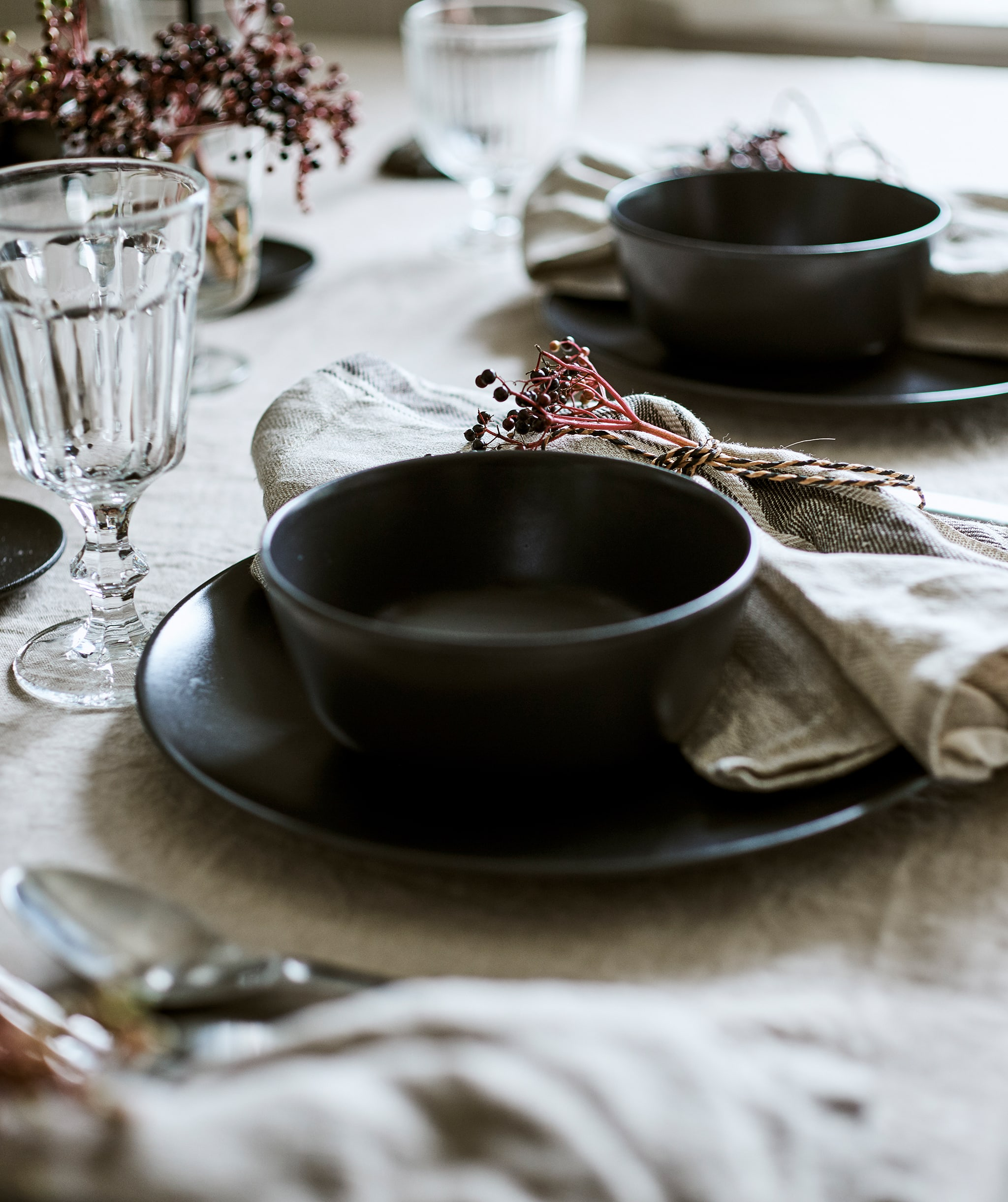 Two place settings on a linen covered table, each has a grey-blue bowl set on a plate with a glass goblet and tied napkin.