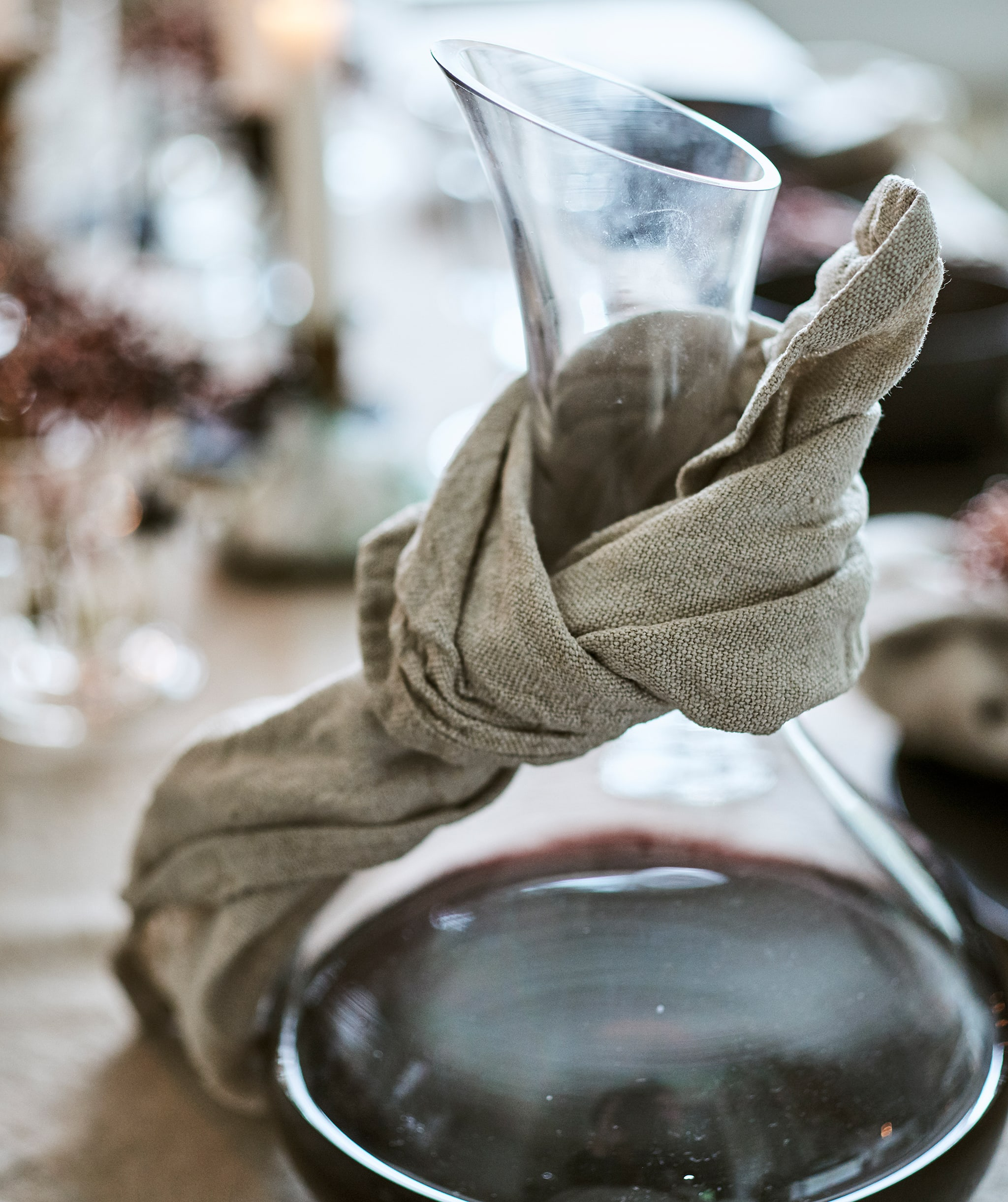 A glass carafe containing red wine with a natural coloured linen napkin tied round the neck to catch drips.