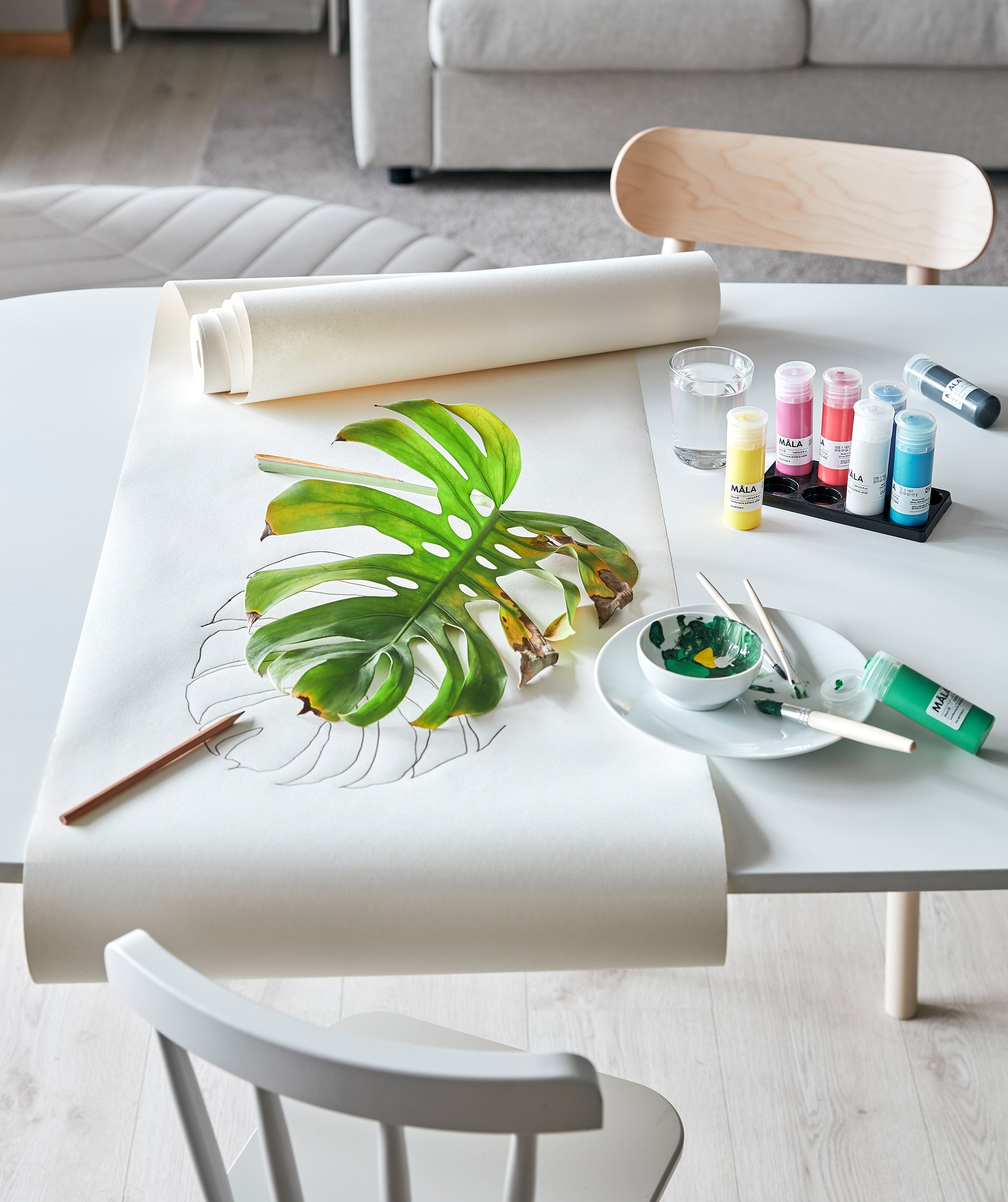 Living room table arranged for a plant-based art session: MÅLA paint, drawing paper and a partly withered MONSTRERA leaf.