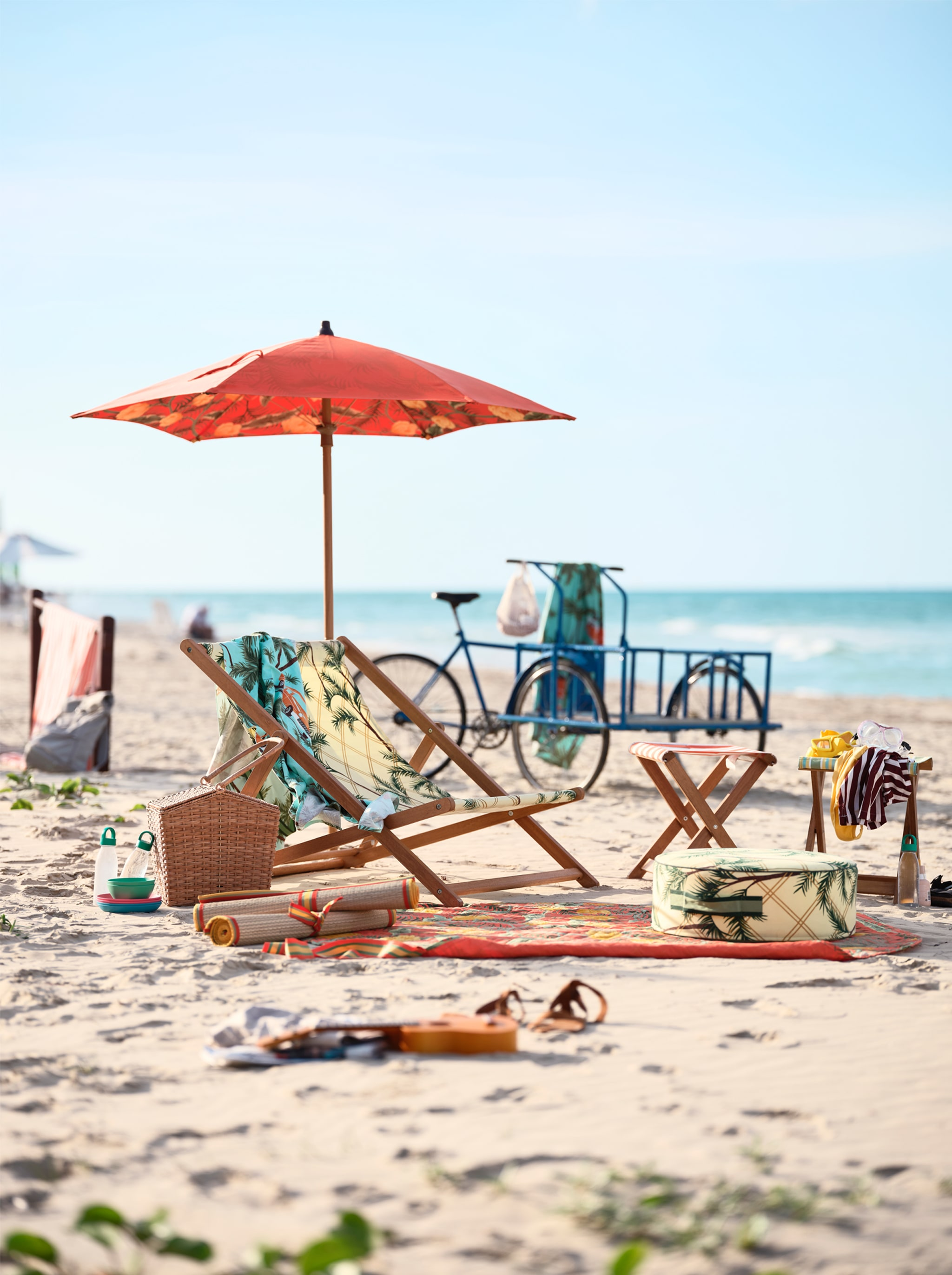 A patterned beach chair with an umbrella and towels, standing on a sandy beach. A blue bicycle stands in the background.