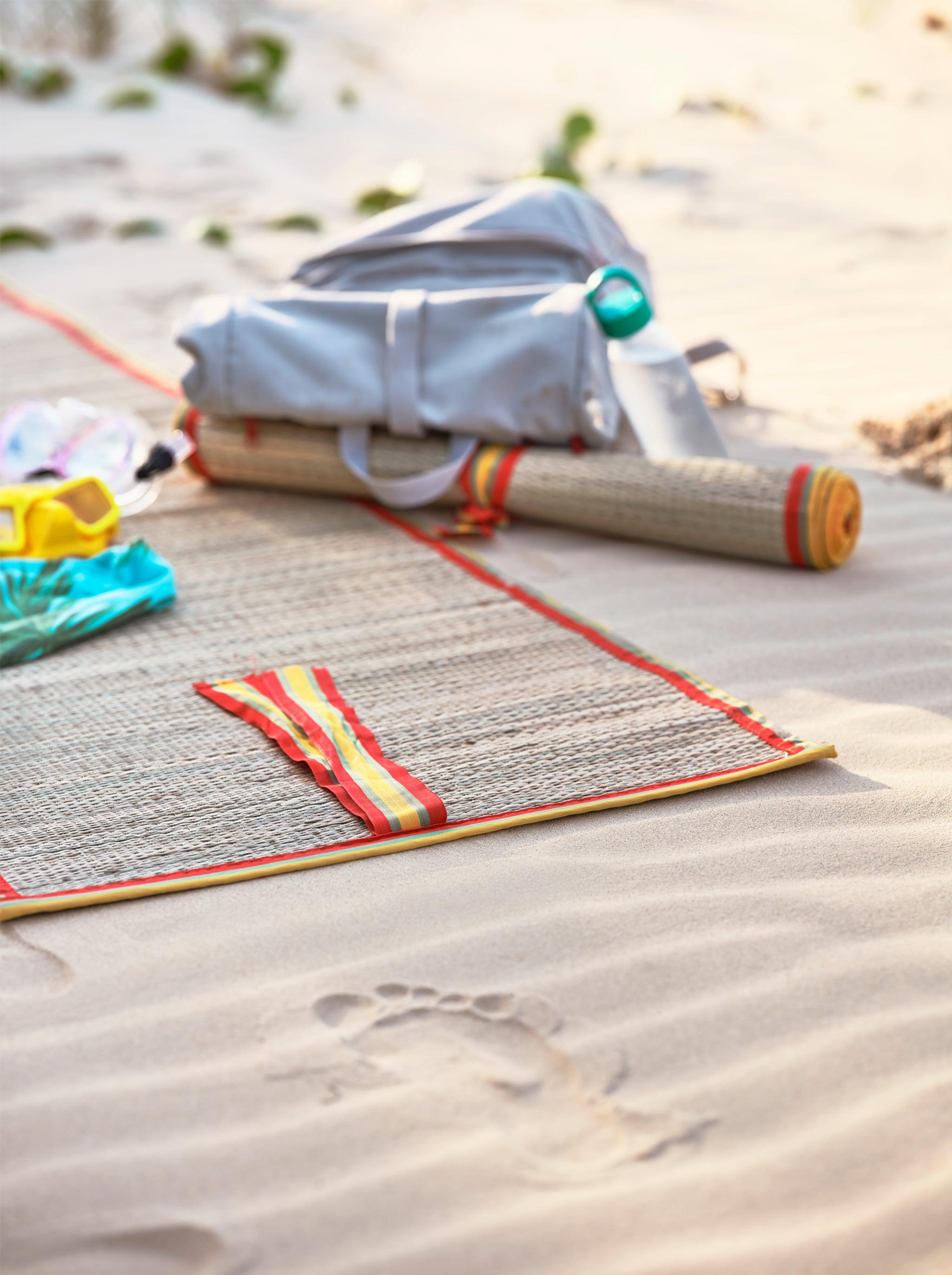 沙灘上舖上黃色和橙色飾邊的編織沙灘墊,旁邊有一個淺灰色背囊。