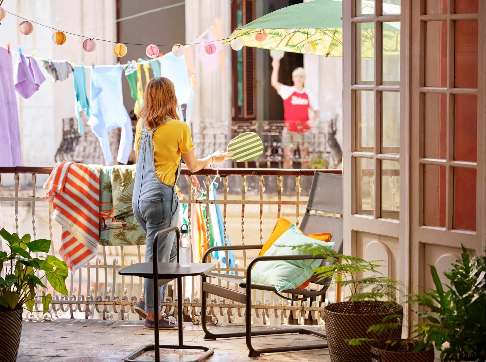 一名女子拿著沙灘球拍靠在露台欄杆,背景掛著一些燈串和衣服。