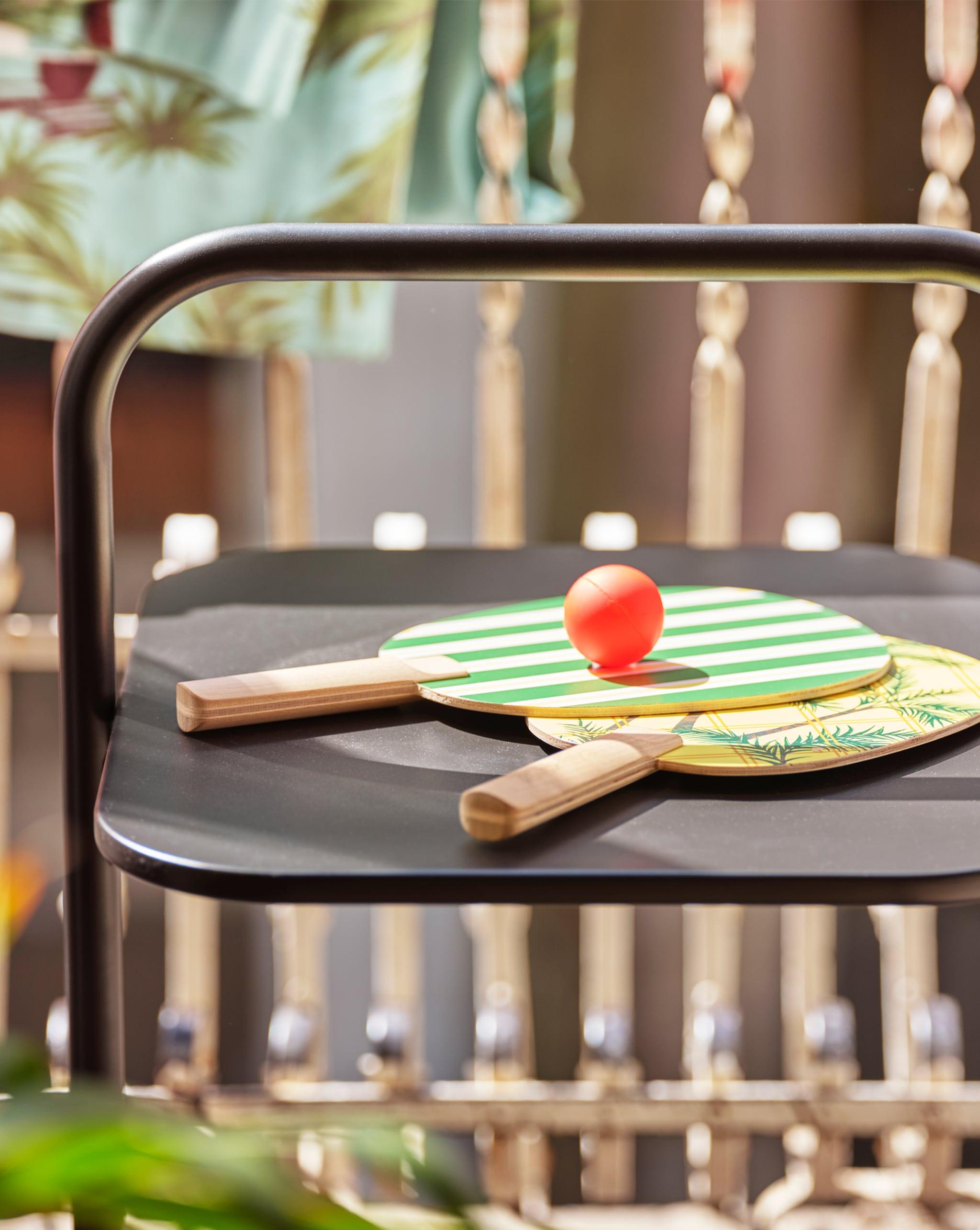 露台上的黑色檯上有兩塊綠色和黃色印花球拍和一個乒乓球。