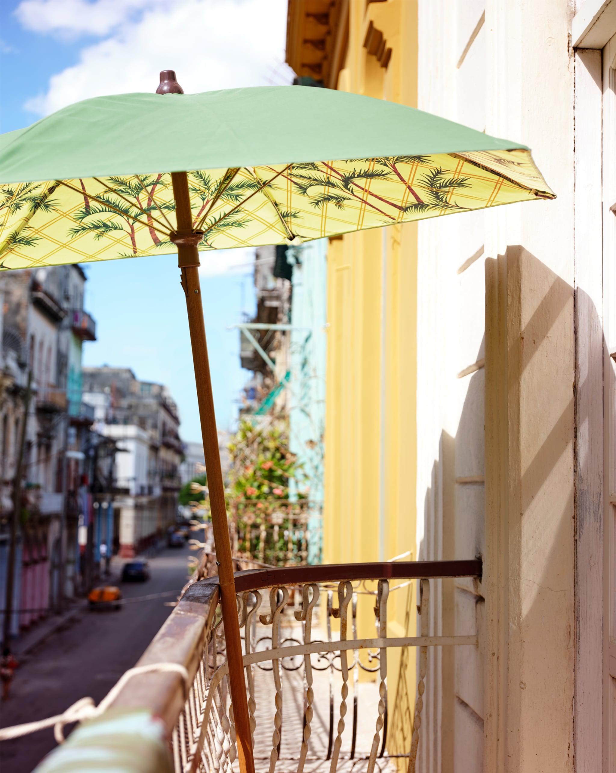 綠色和黃色印花圖案太陽傘靠在露台欄杆,下面是街景。