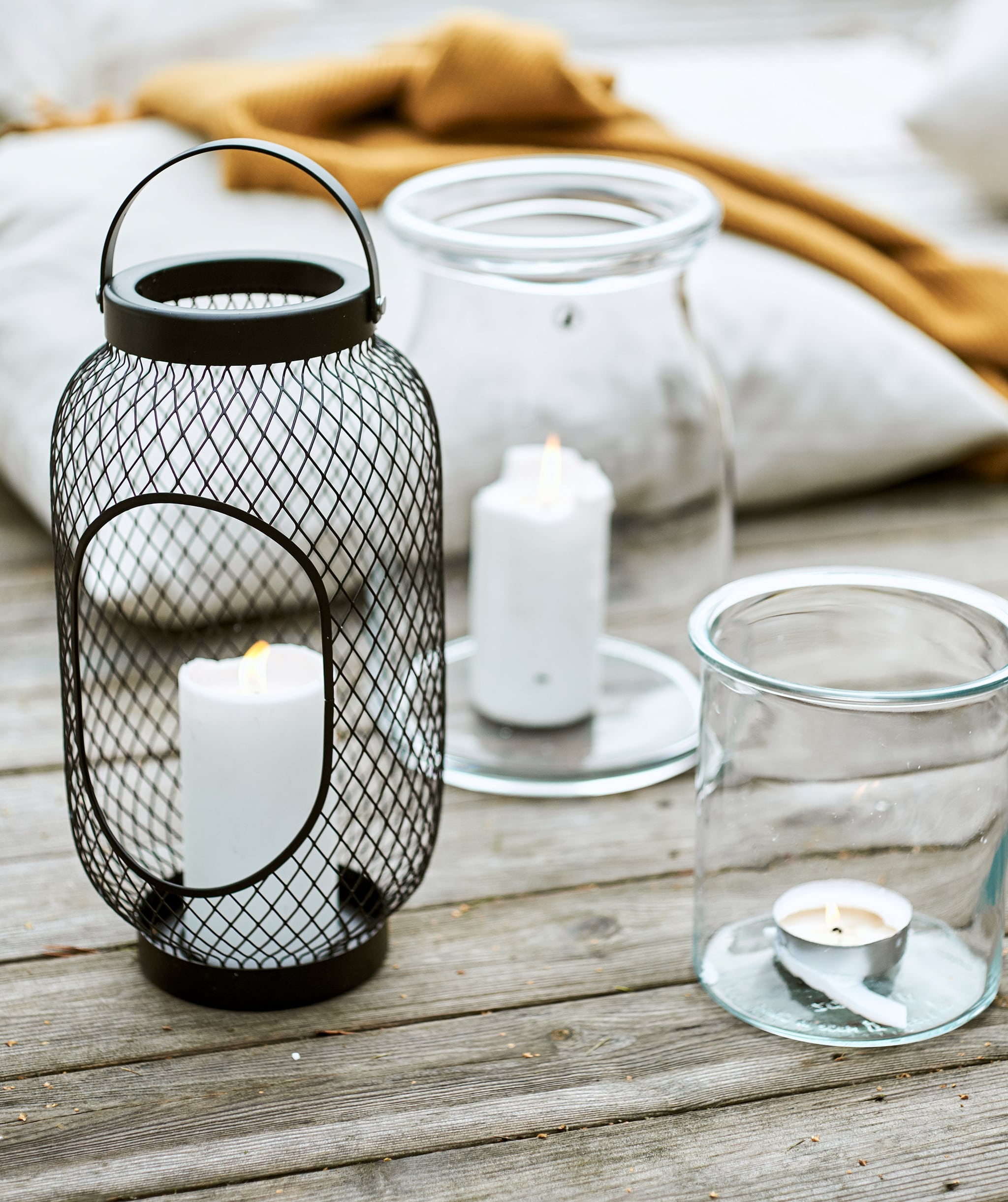 Black mesh wire lantern with block candle beside two glass jars with candles, next to a cushion and yellow throw on decking.