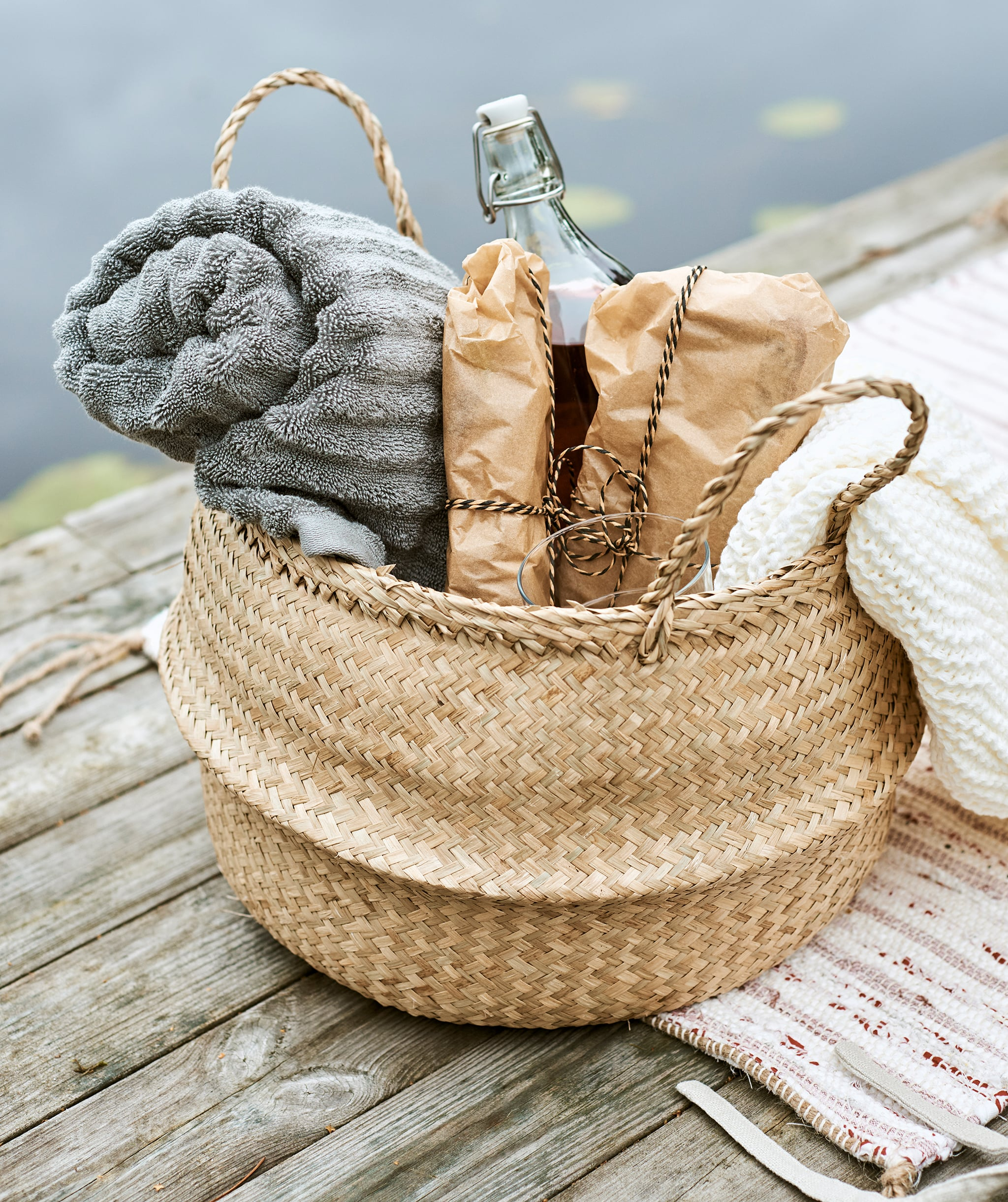 A woven basket packed for a picnic with rolled-up grey towel, sandwiches wrapped in paper, a cream throw and bottle of drink.