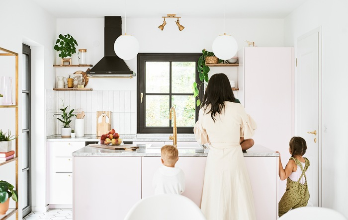A mother and two children stand at the kitchen island in a kitchen with pink cabinets, marble worktops and brass fixtures.
