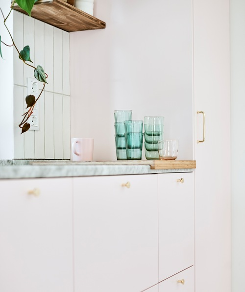 Row of pink-doored kitchen units with a stack of green glasses and a pink mug on a chopping board on the marble worktop.