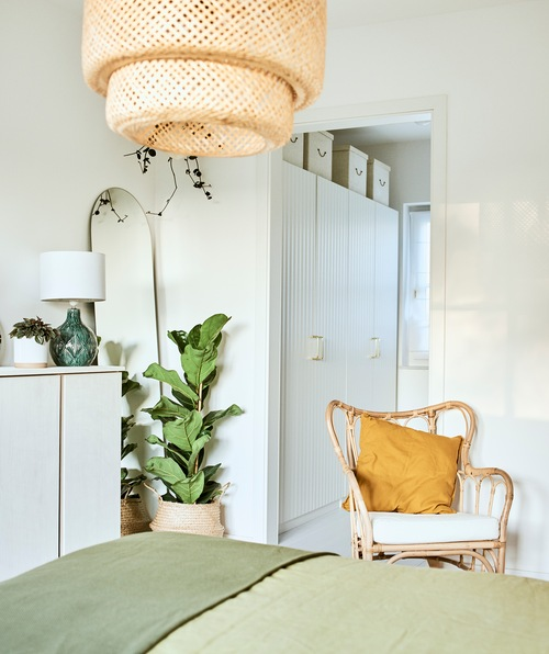 A bed with green linen in a room with a wicker armchair and woven ceiling lamp and an alcove with a run of white wardrobes.