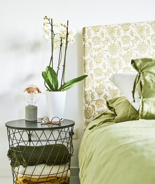 Green bed linen on a bed with a headboard made of green paisley fabric, specs and an orchid sit on the wire bedside table.