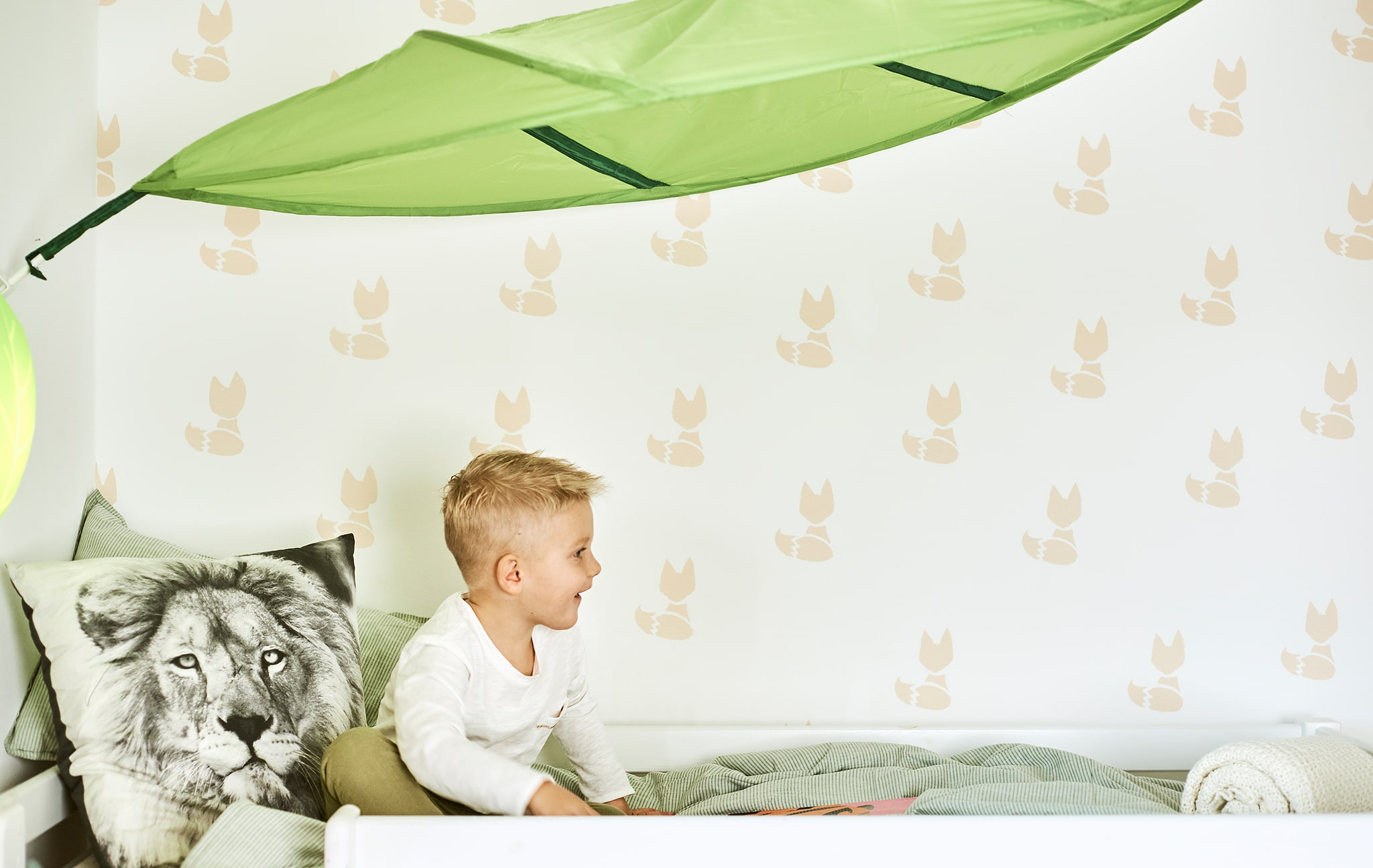 A child sits on a bed with green duvet and a cushion printed with a lion's face, above the bed is a green leaf-shaped canopy.