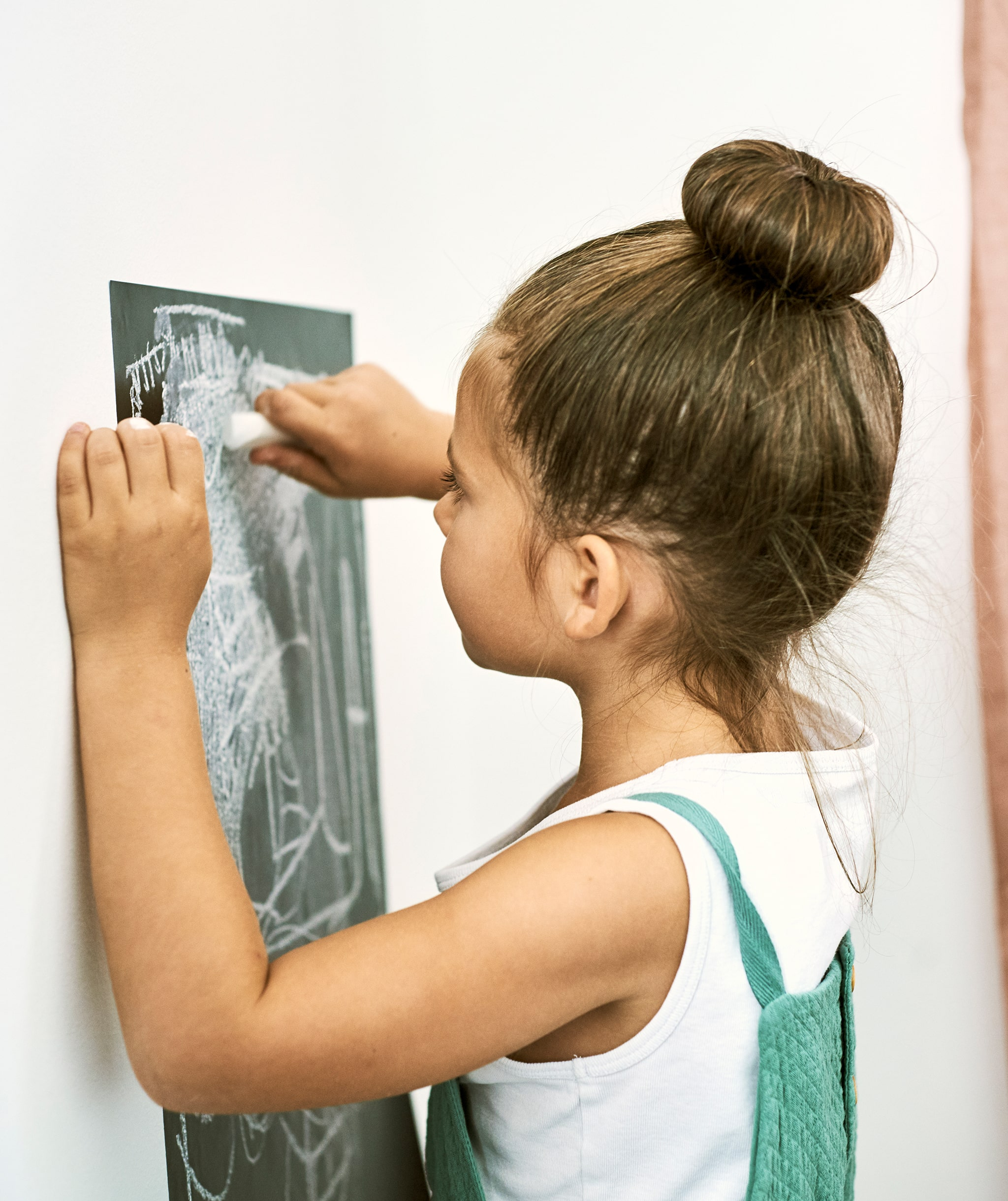 A girl uses a stick of chalk to draw on a chalkboard wall sticker that is stuck to a white wall.