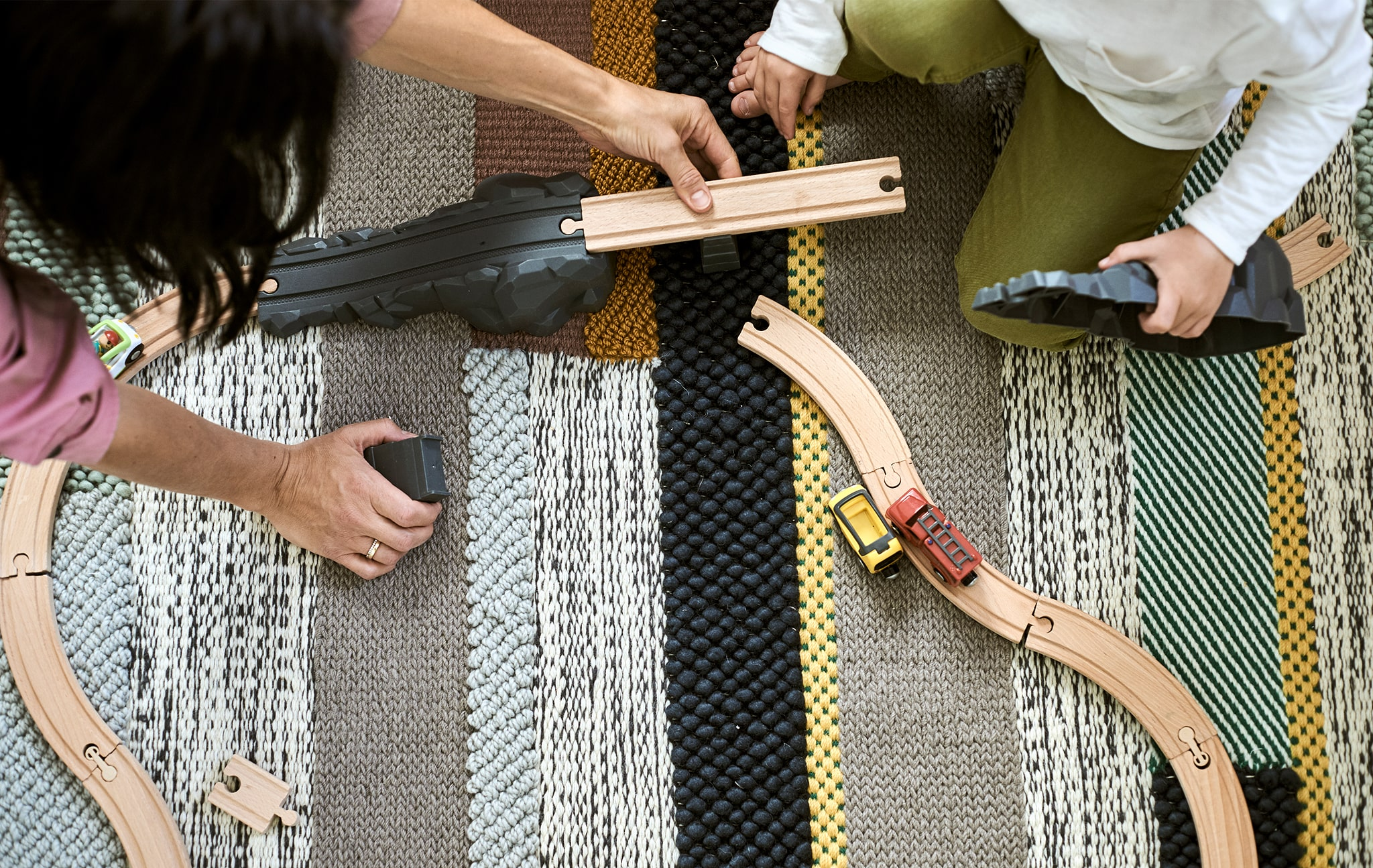 A mum and son build a wood road track together on a rug woven with different coloured stripes.