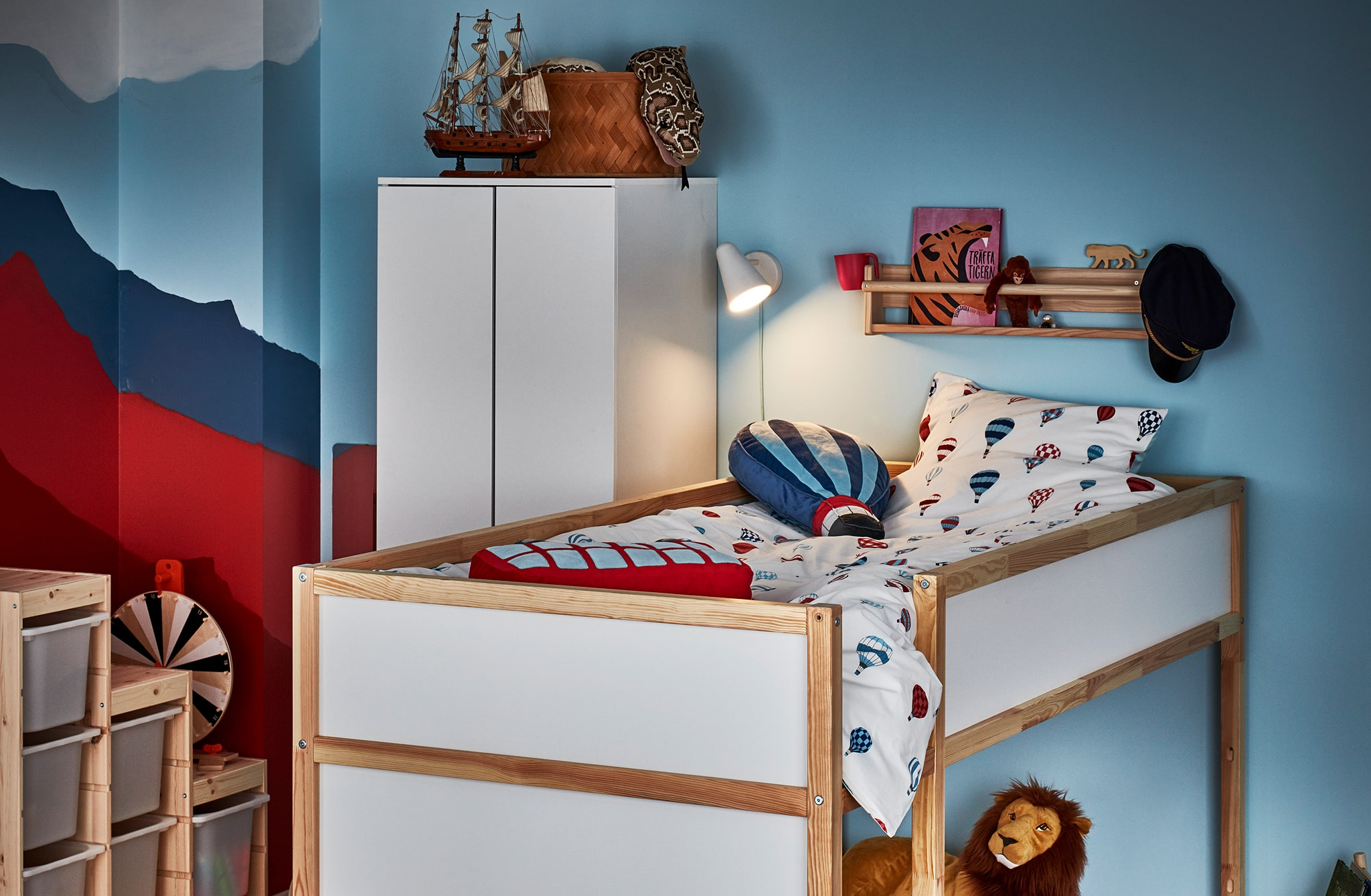 Corner of a child's room with a reversible bed in loft position, a ledge shelf with book and toys, lit bedlight.