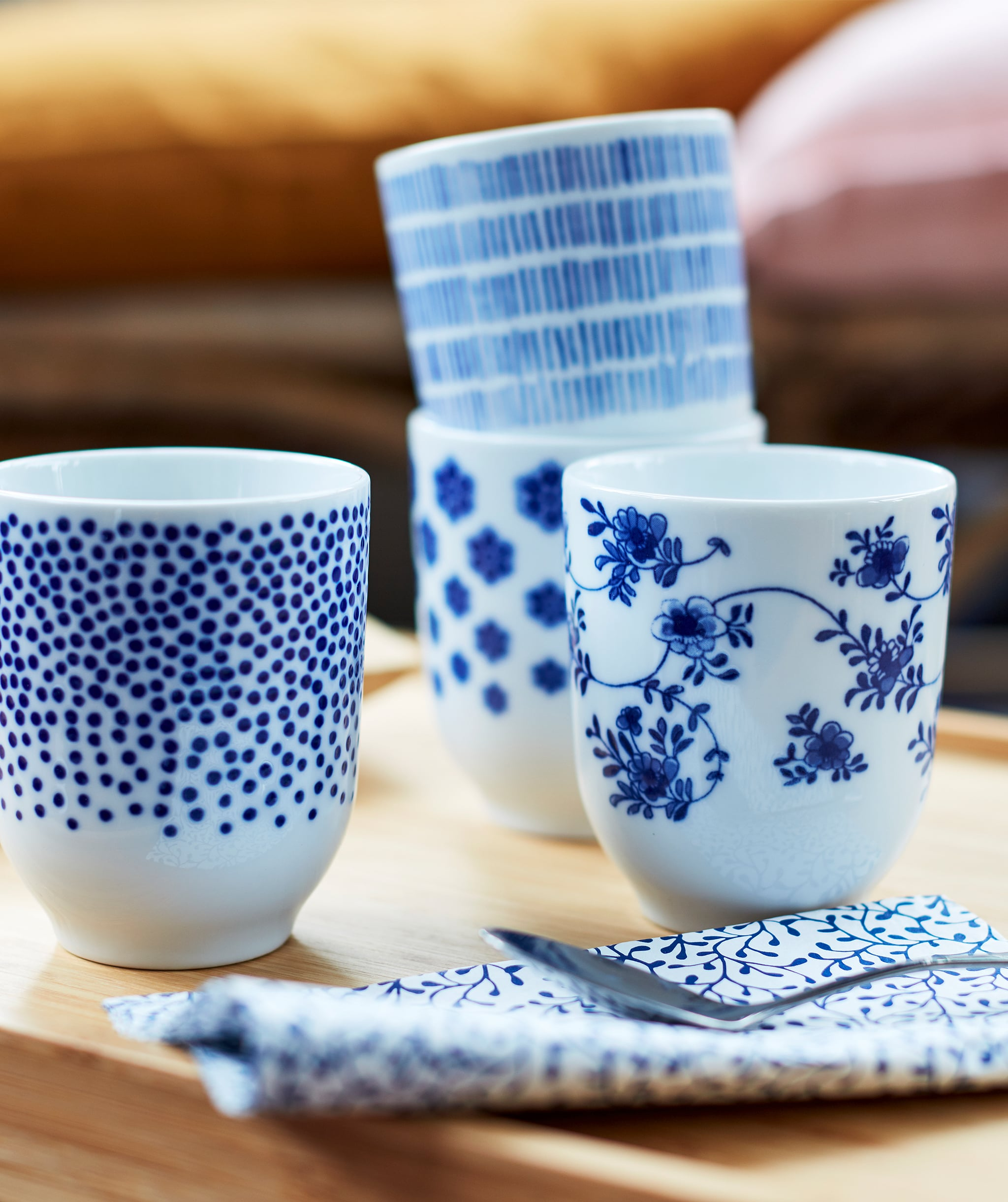 Four small tea mugs in white, decorated with different patterns in dark blue.