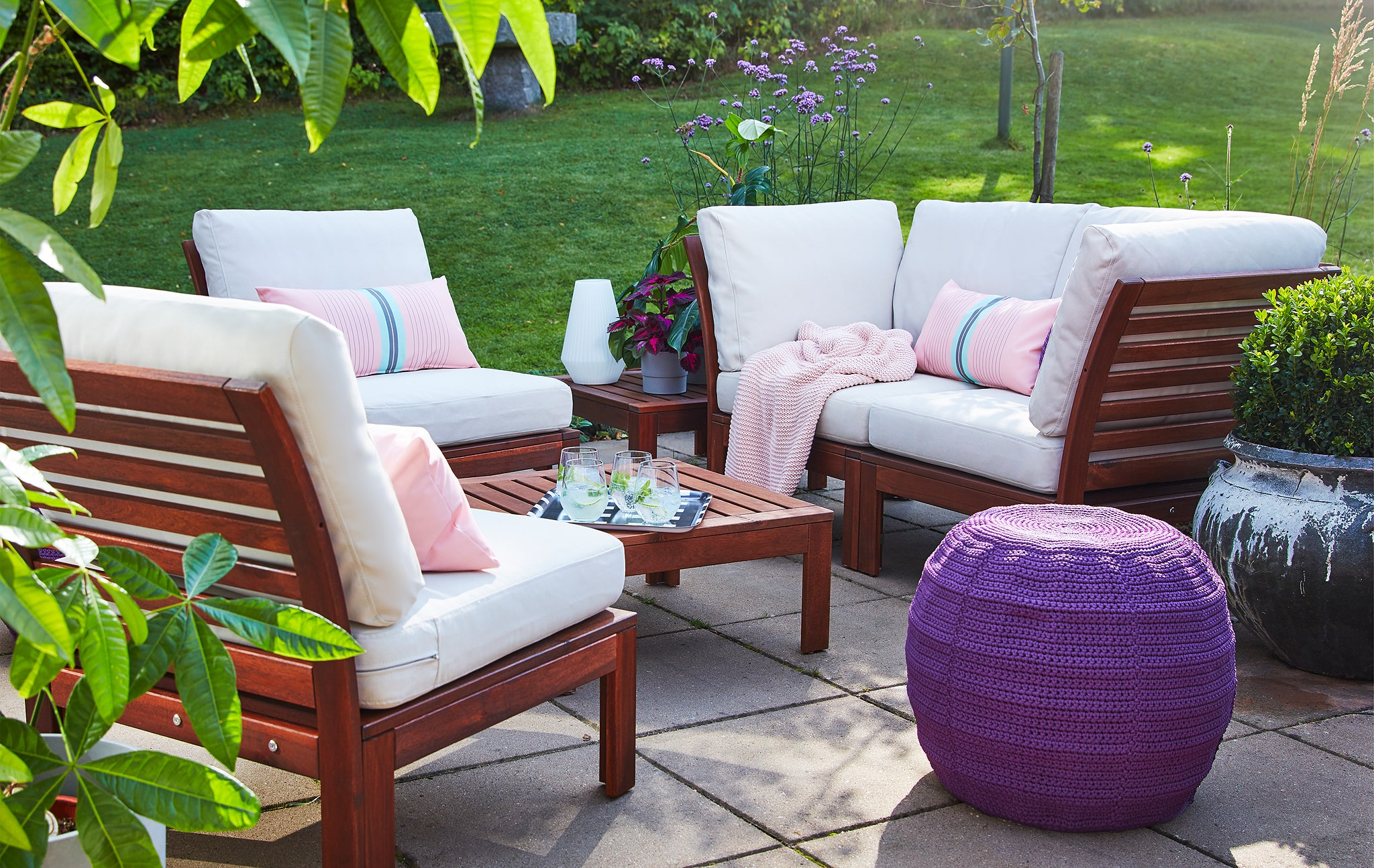 Wooden outdoor furniture with white and pink cushions, shown on a grey stone terrace.