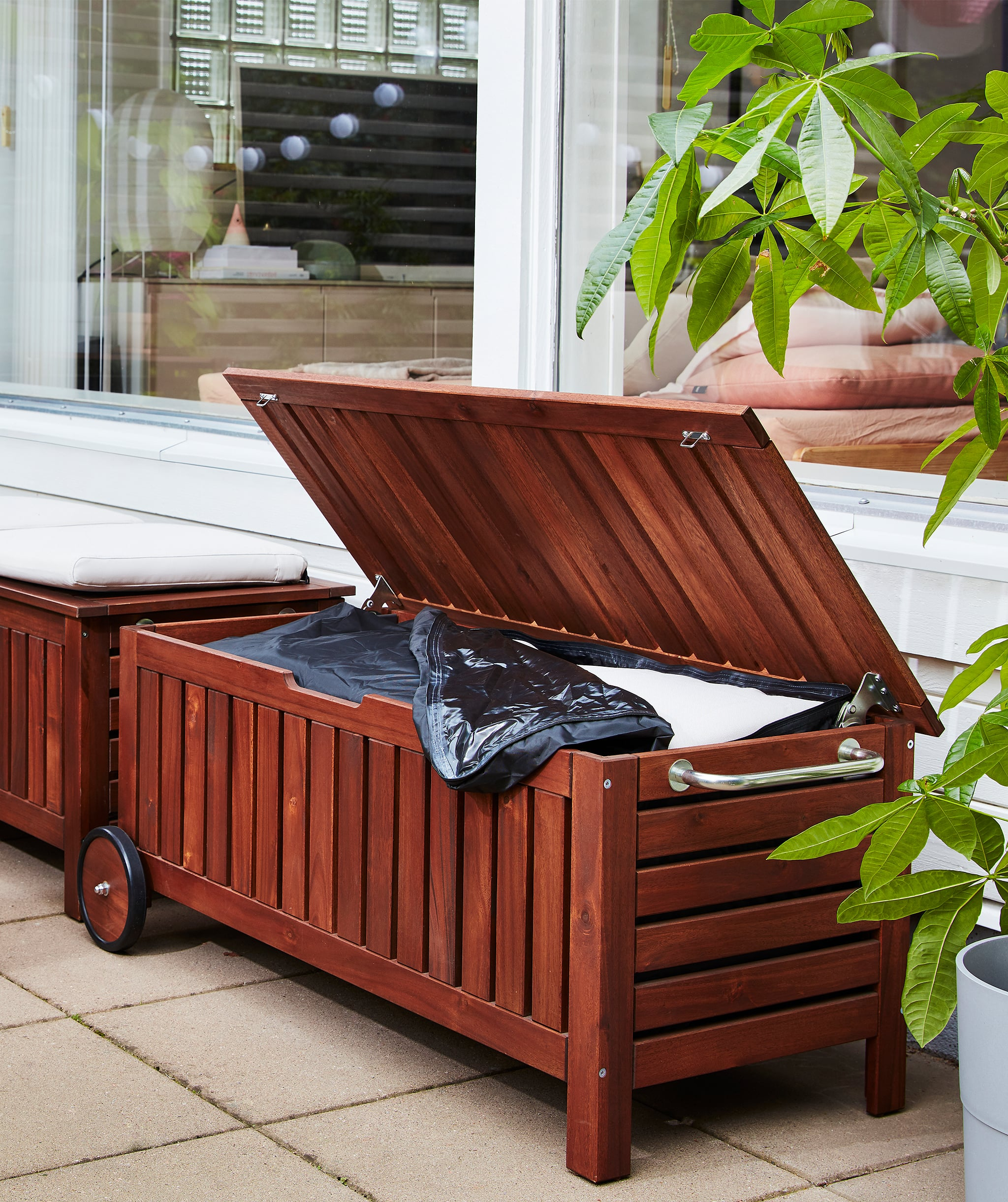 Two dark wooden storage benches on a terrace. One has its lid open and shows outdoor cushions inside.
