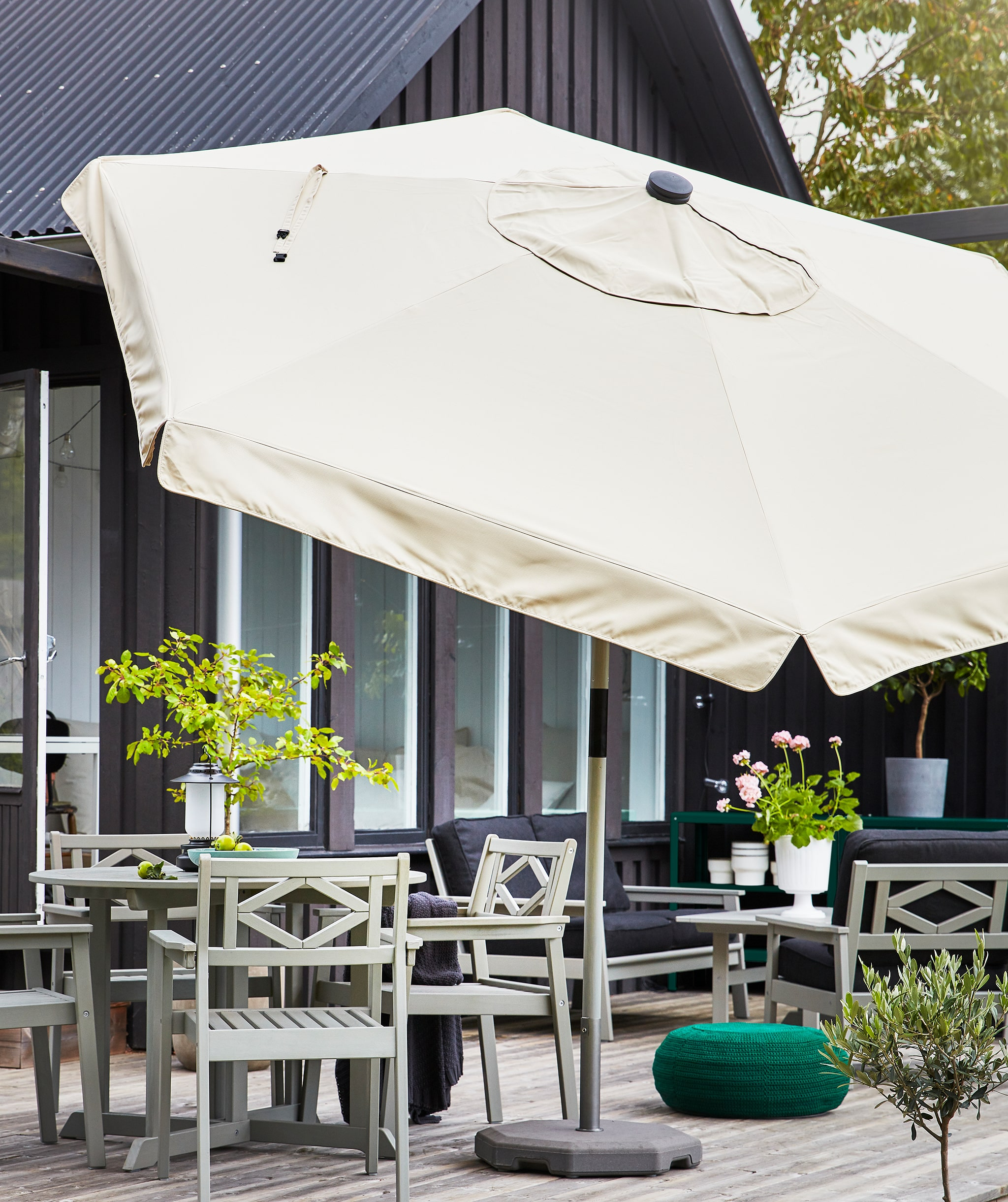A large parasol in beige standing on a terrace with grey outdoor furniture and plants.