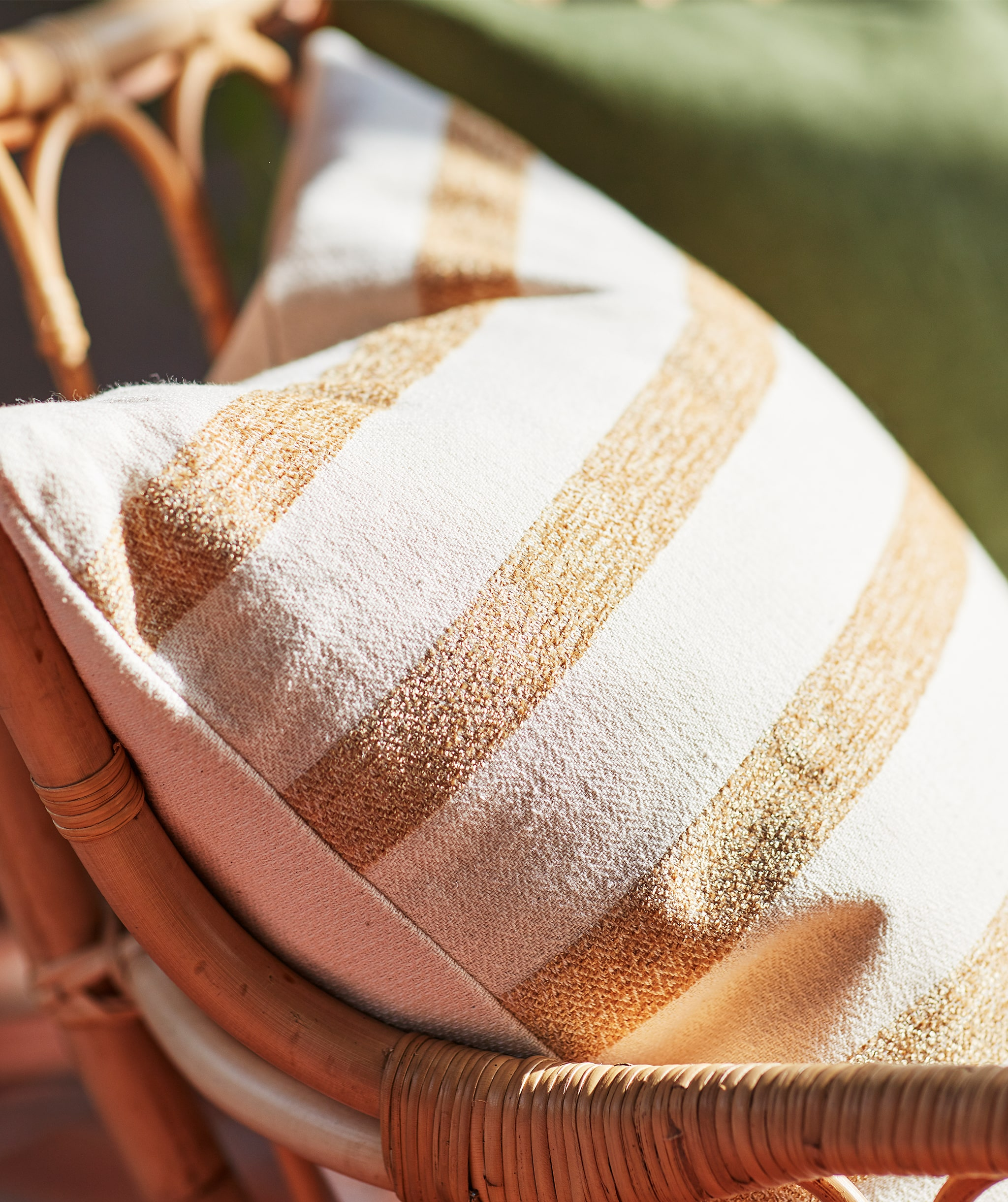 Close-up of a striped cotton pillow in beige and light brown in a rattan chair.