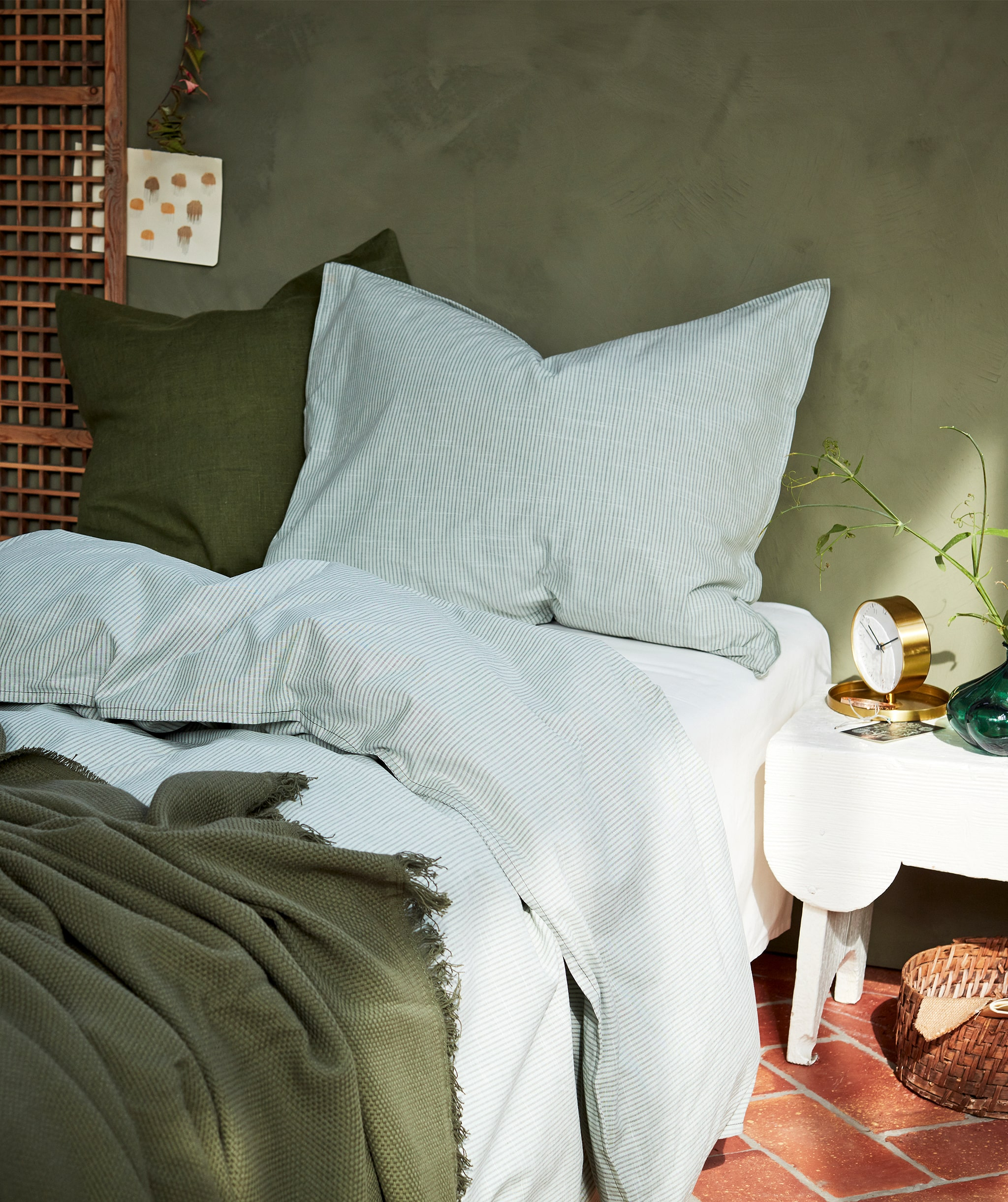 A cosy bed with bedlinen in white and green, two large pillows and rays of daylight coming in from the right.
