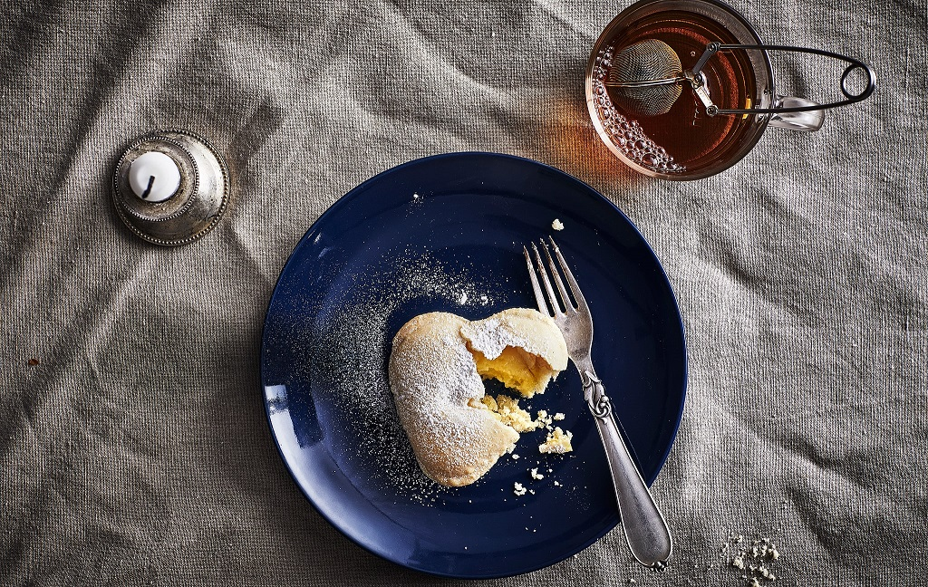 A vanilla heart biscuit and a fork on a dark blue plate, a mug with tea and a candle.